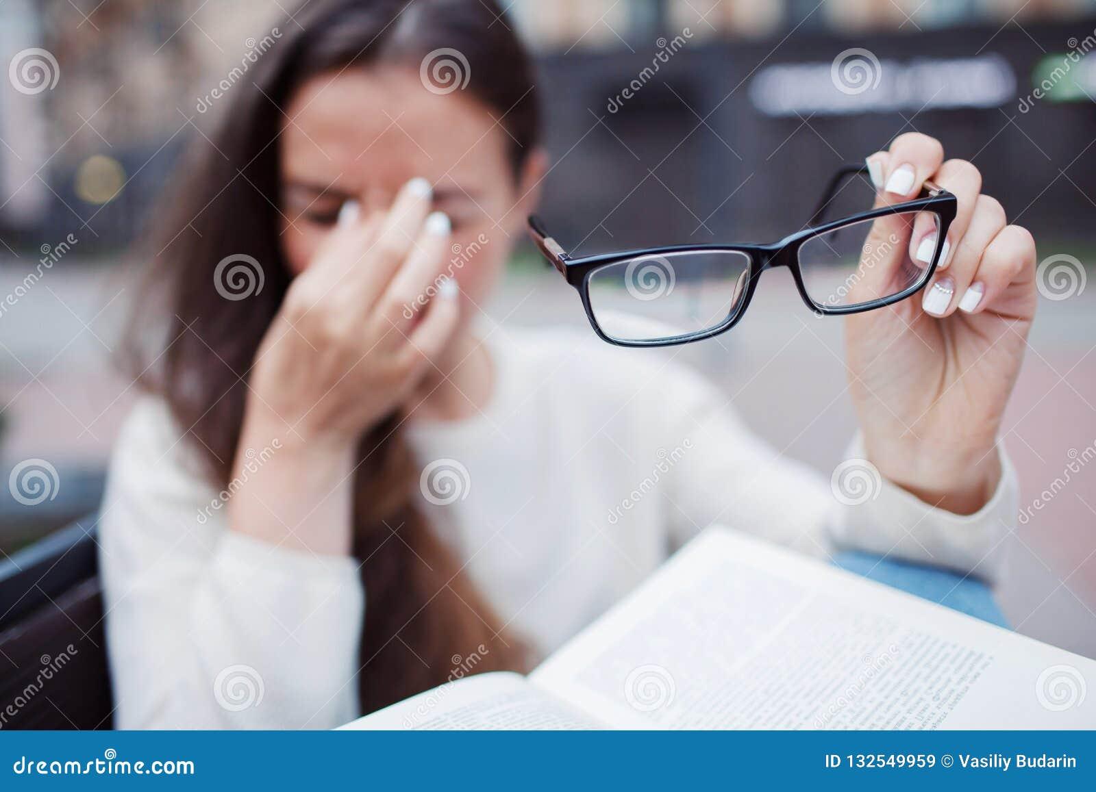 Close-upportret van aantrekkelijk wijfje met in hand oogglazen Het slechte jonge meisje heeft kwesties met visie Zij wrijft haar