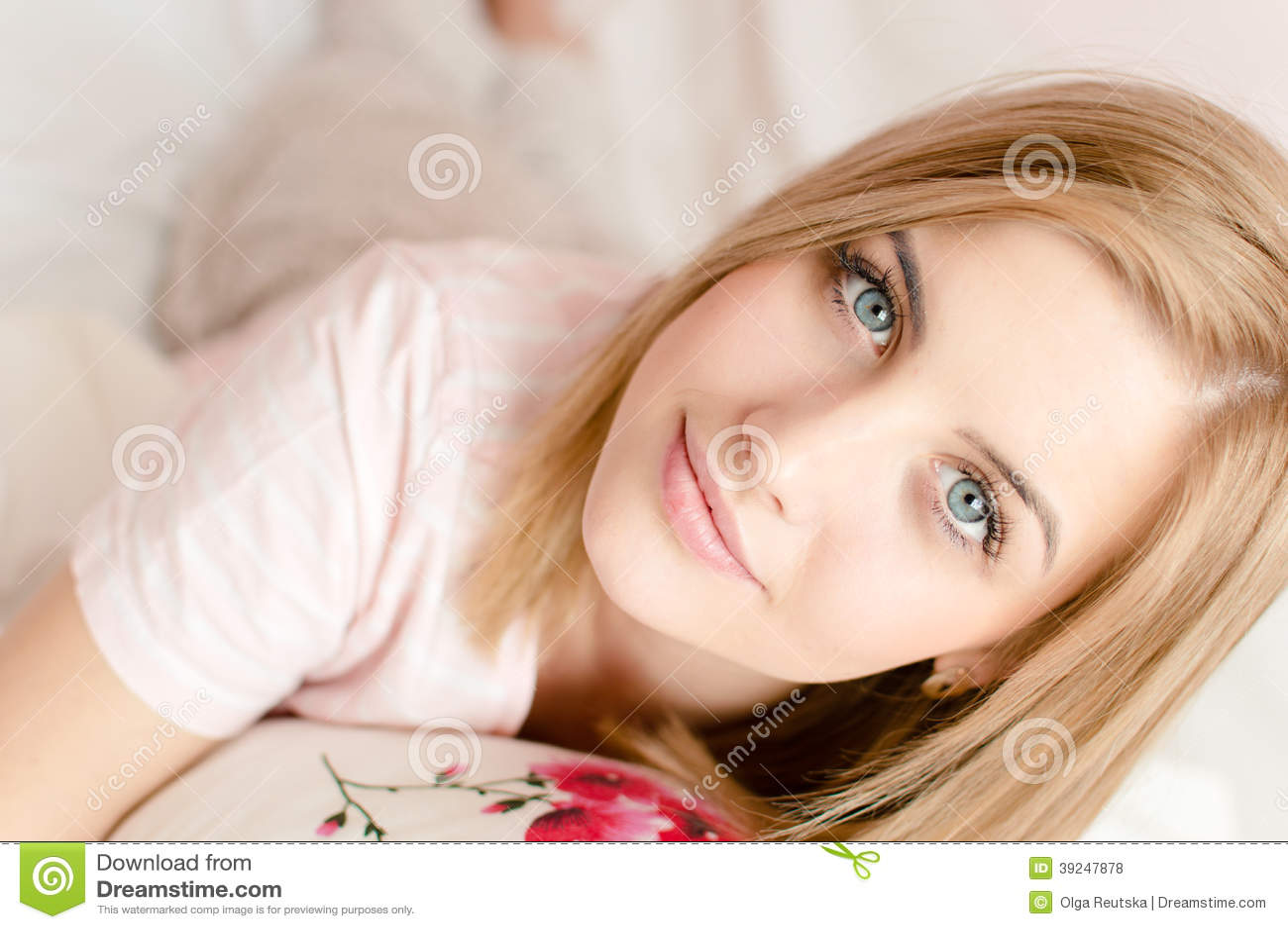 Close-upportret van aantrekkelijke mooie jonge blonde vrouw met blauwe ogen en uitstekende huid in bed & het bekijken camera
