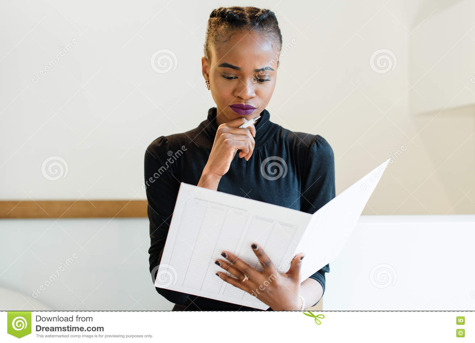 Close-upportret van denkende succesvolle Afrikaanse of zwarte Amerikaanse bedrijfsvrouw die een grote witte dossier en een pen ho