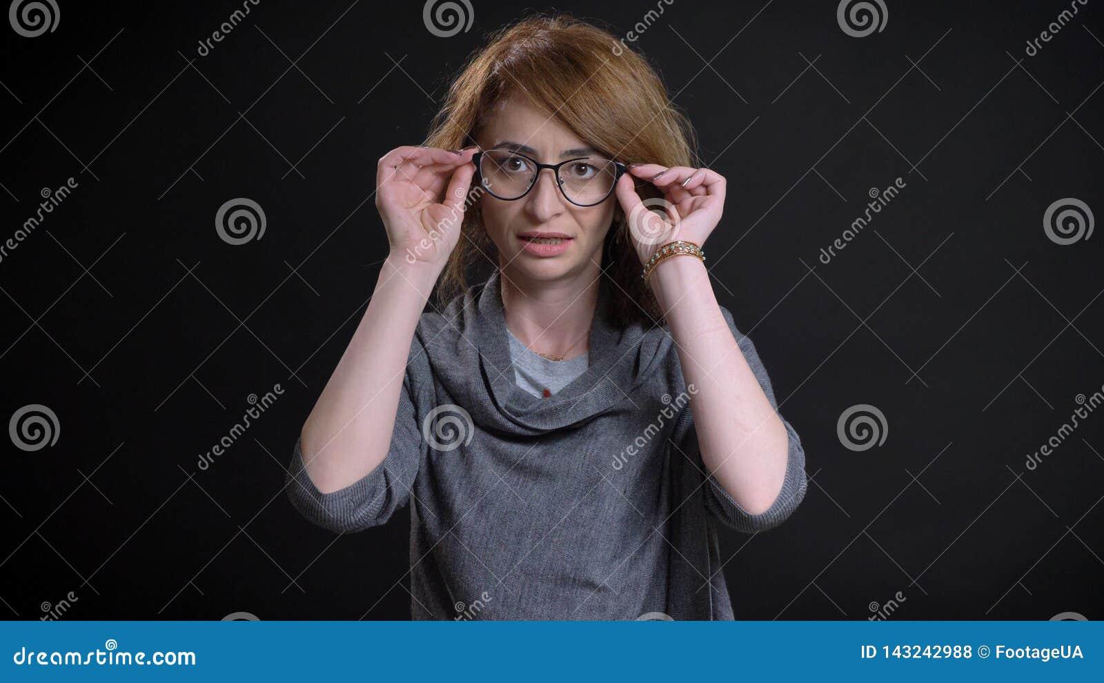 Close-upportret van extravagant roodharigewijfje die op middelbare leeftijd recht camera bekijken die haar glazen met achtergrond