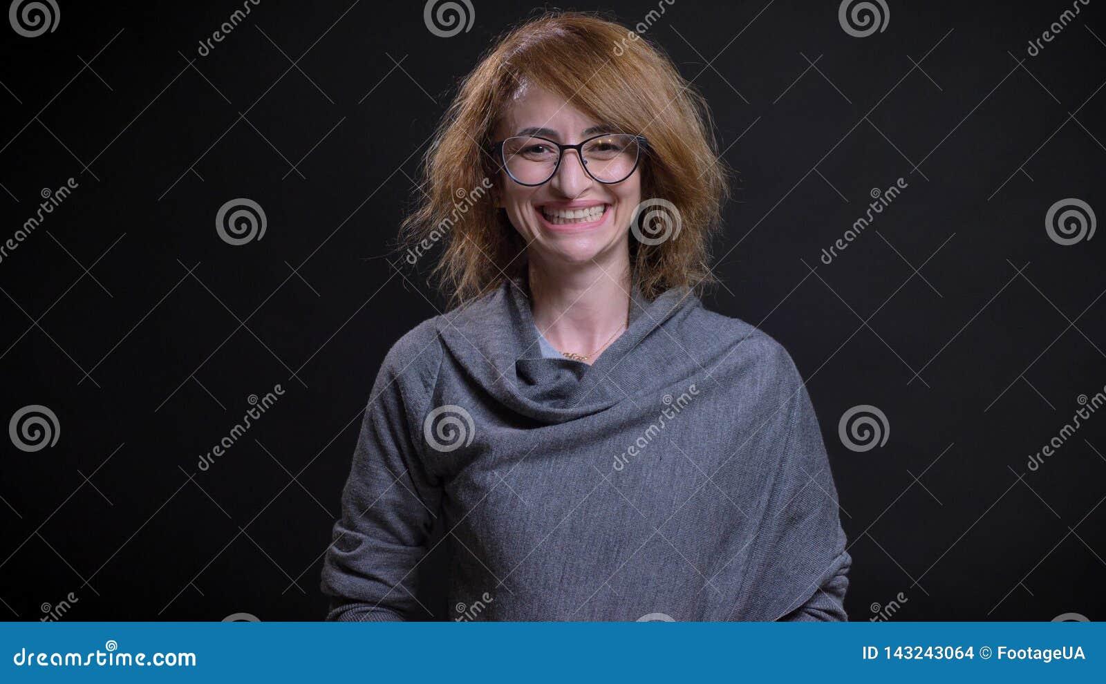 Close-upportret van extravagant roodharigewijfje op middelbare leeftijd in gelukkig en glazen die cheerfully terwijl het kijken z