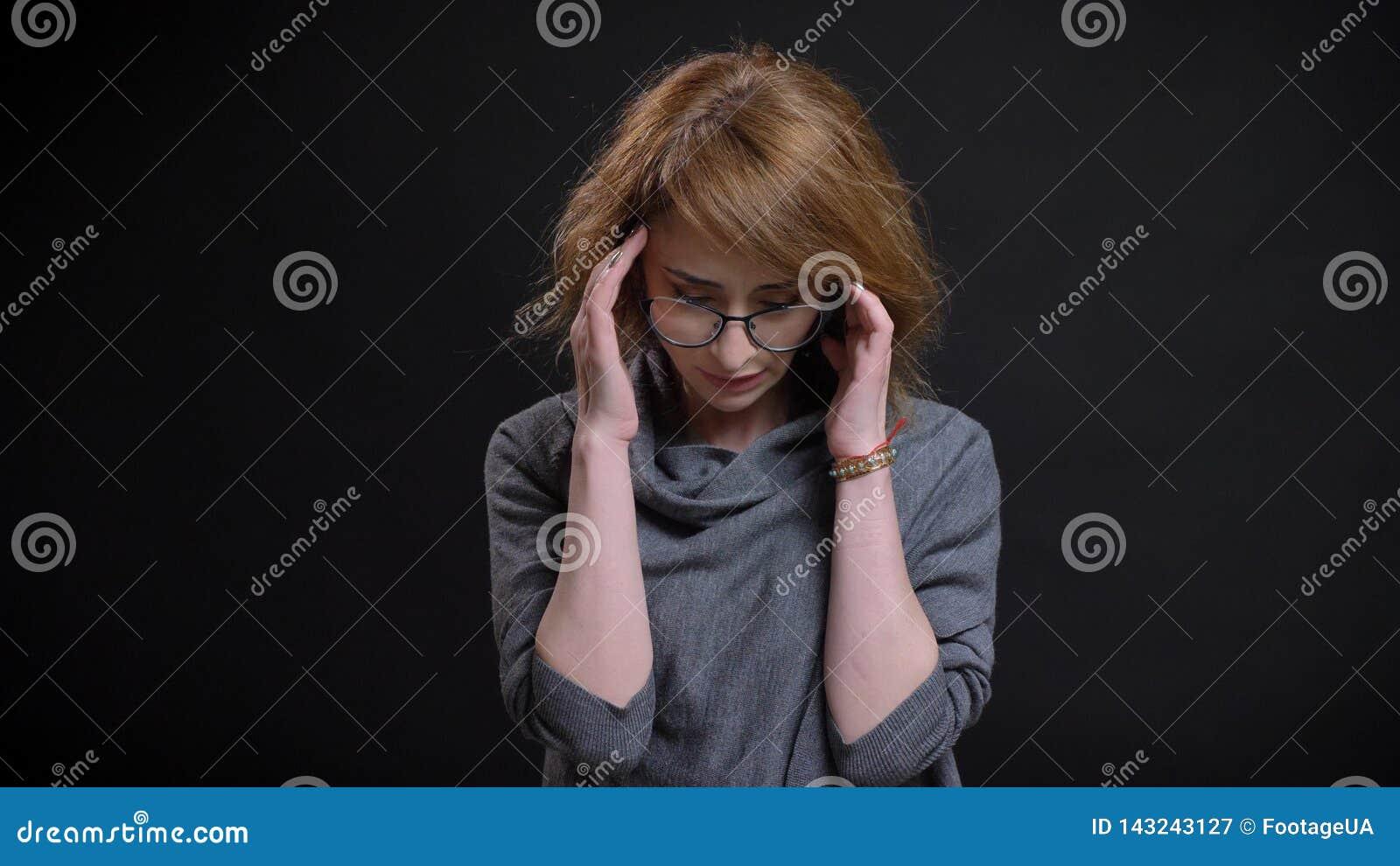 Close-upportret van extravagant roodharigewijfje op middelbare leeftijd in glazen die een hoofdpijn hebben en voor worden vermoei