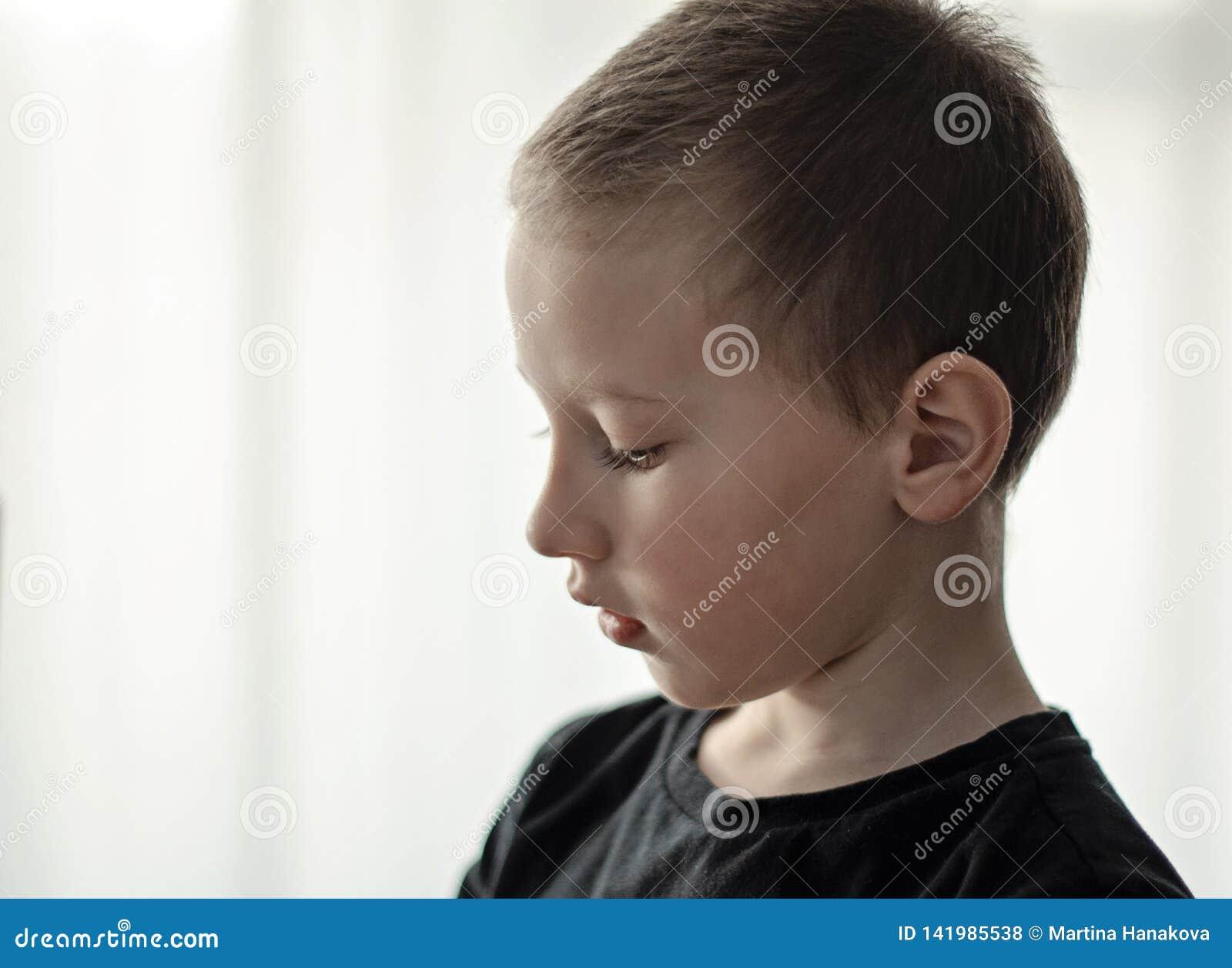 Close-upportret van gedeprimeerde jonge pre-school jongen in zwarte beneden en t-shirt die kijken denken Ongelukkig alleen kind m