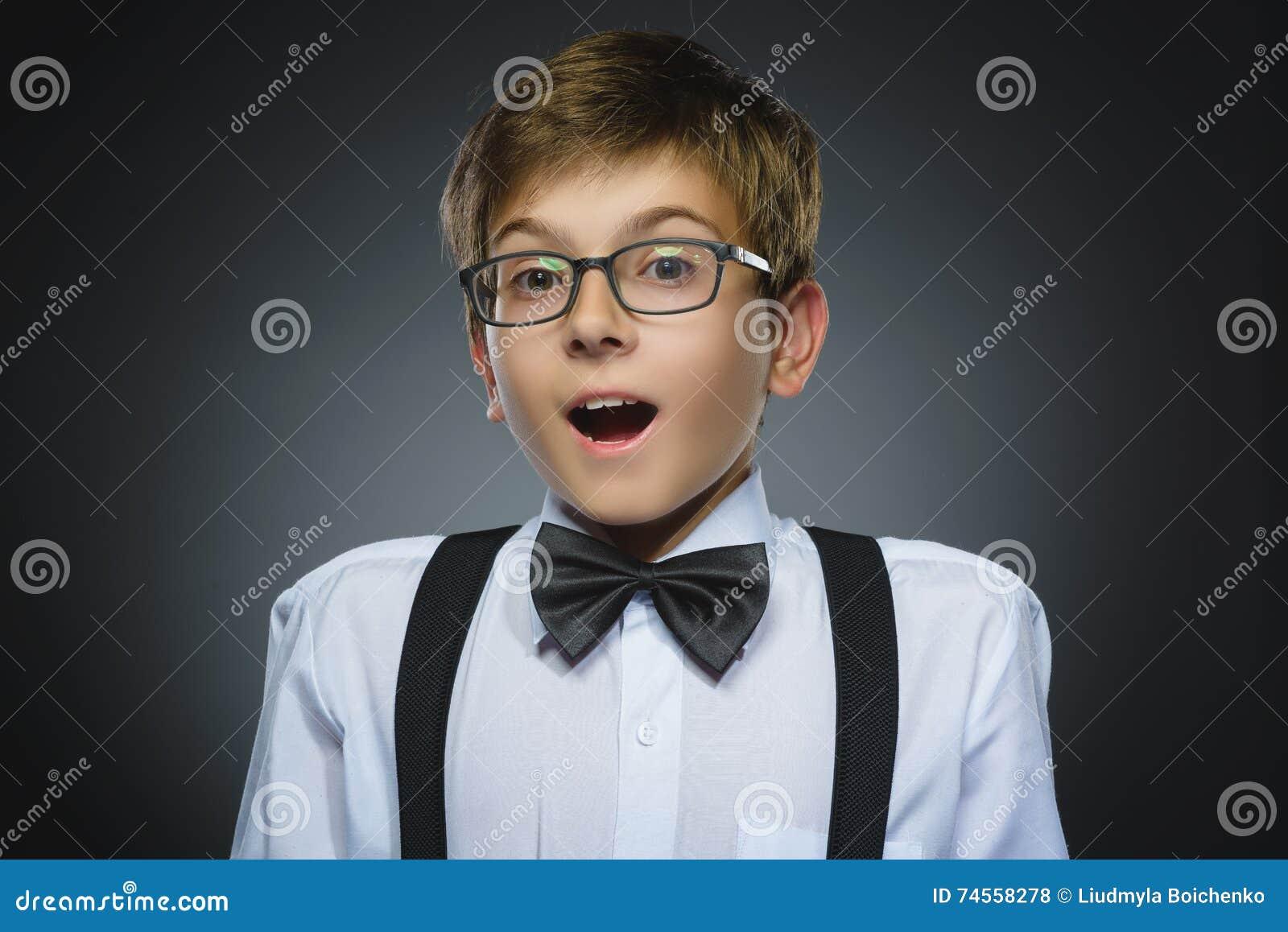 Close-upportret van gelukkige jongens gaande die verrassing op grijze achtergrond wordt geïsoleerd