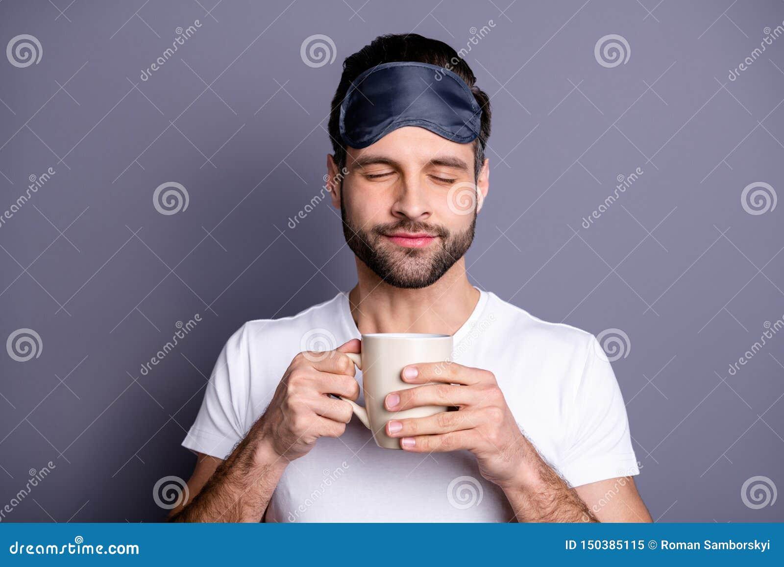 Close-upportret van van hem overvalt hij mooie aantrekkelijke kalme gebaarde kerelholding in handen ruikend espressoaroma