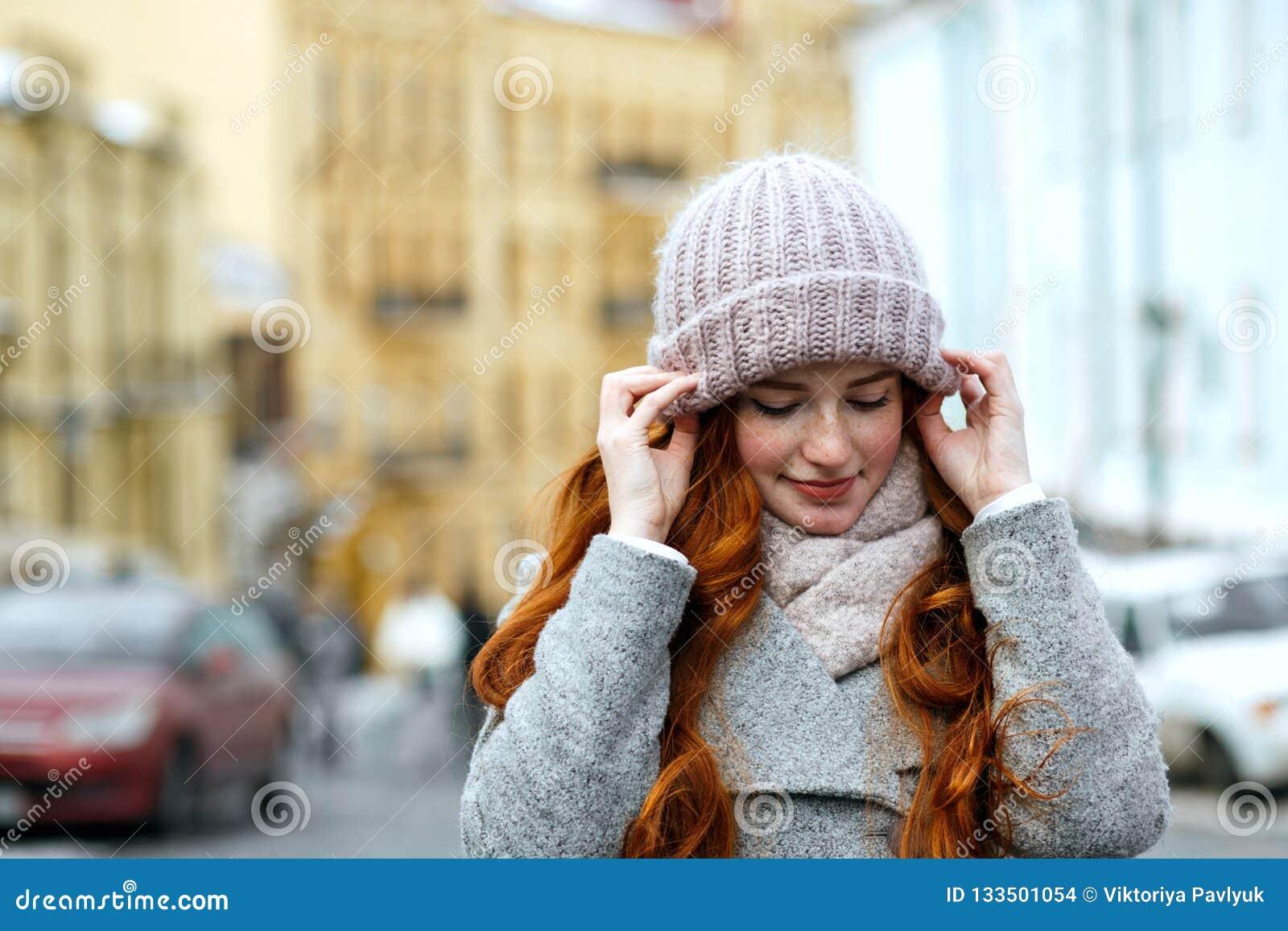 Close-upportret van het verbazen van rood haired meisje die gebreide warm dragen