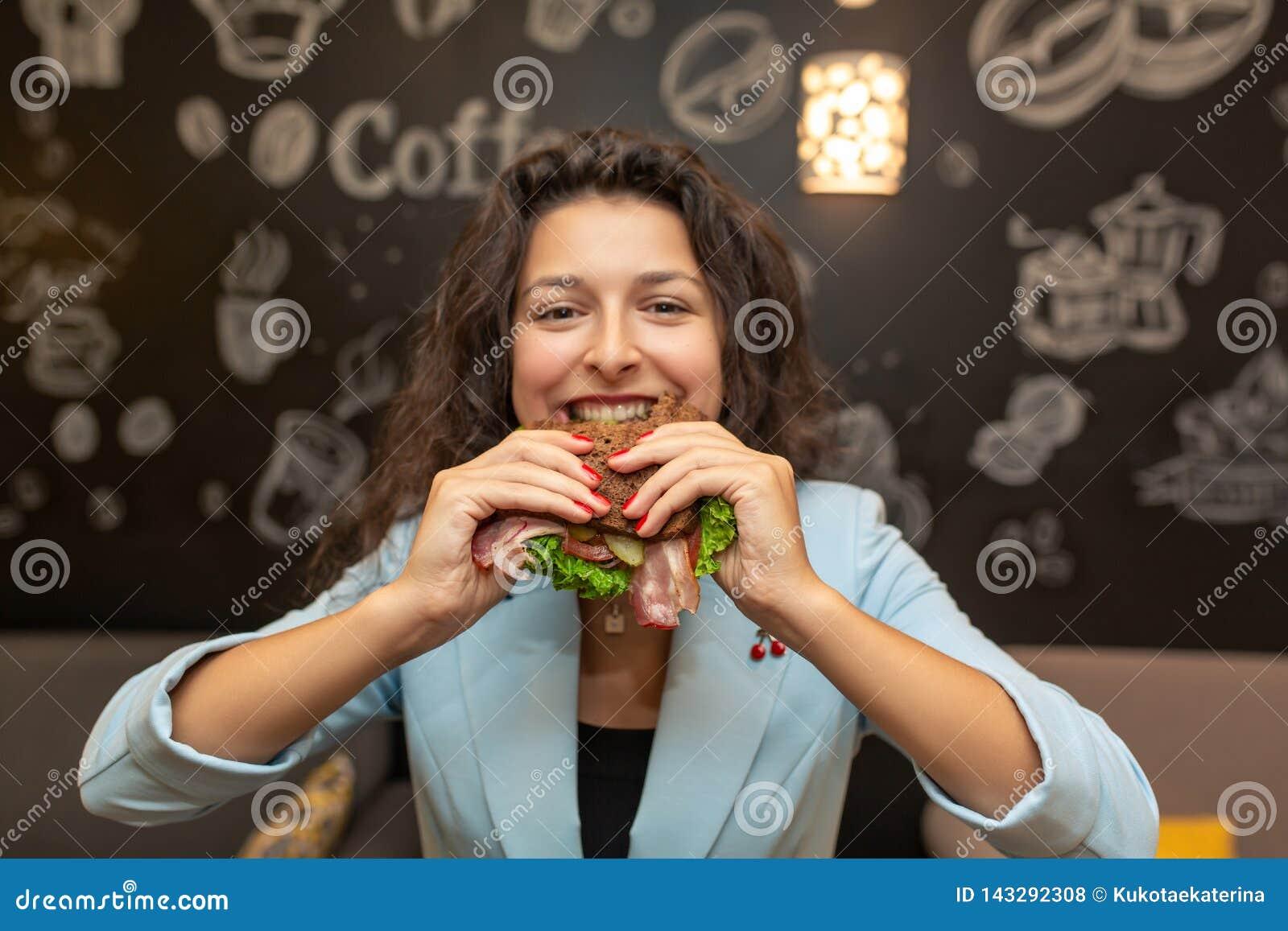 Close-upportret van hongerige jonge Kaukasische vrouw, beetsandwich