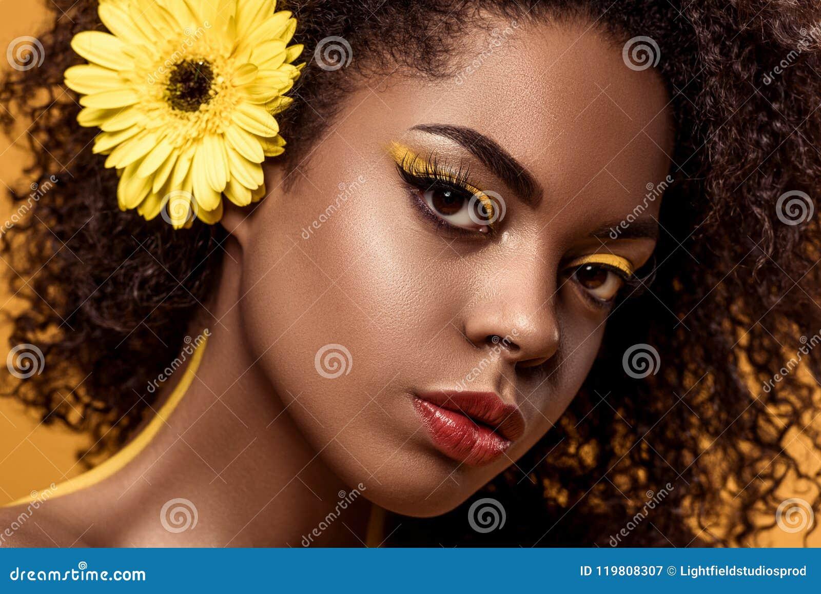 Close-upportret van jonge sensuele Afrikaanse Amerikaanse vrouw met artistieke samenstelling en gerbera in haar