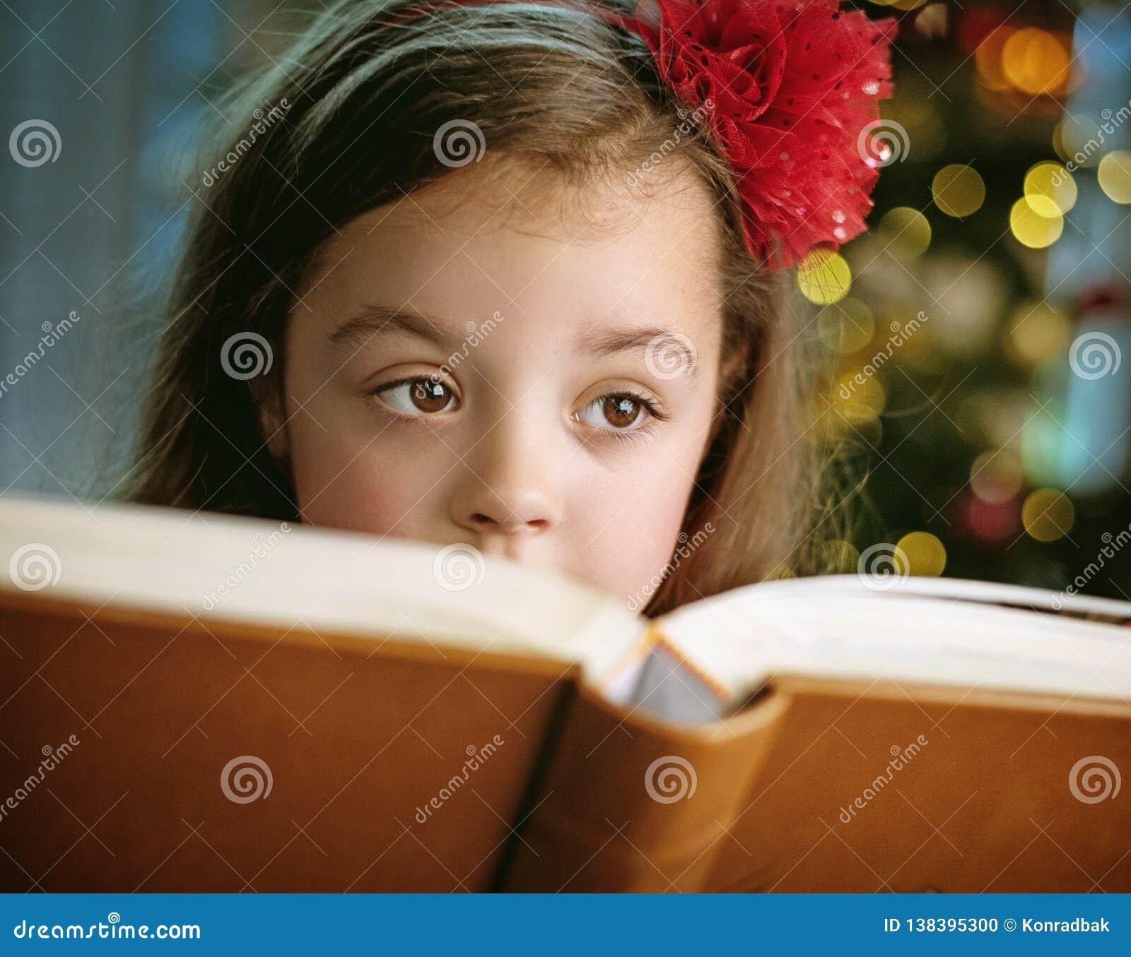 Close-upportret van leuk, meisje die een boek lezen