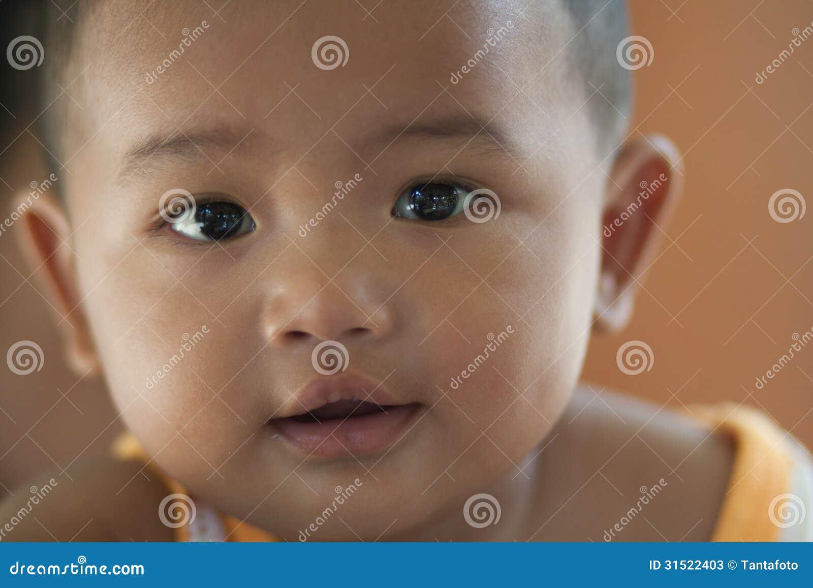 Close-upportret van 10 maand het oude baby bepalen die de camera met mooie ogen bekijken