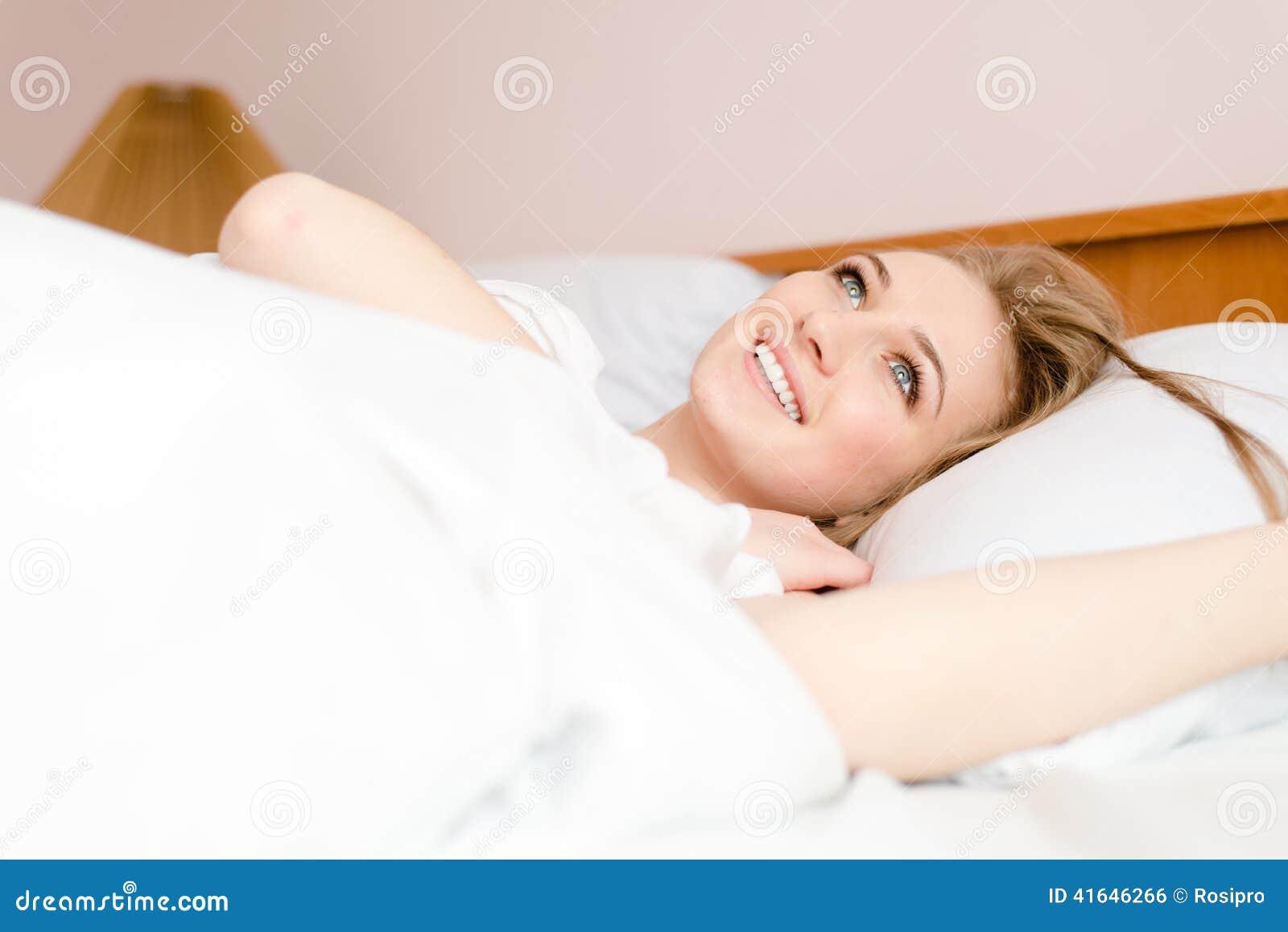 Close-upportret van mooie blonde jonge vrouw die pret het gelukkige glimlachen hebben die in wit bed liggen