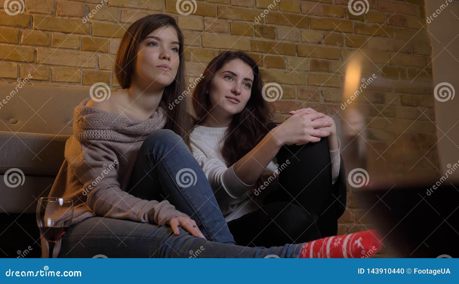 Close-upportret van twee jonge mooie vrouwen die TV-op het koelen met wijnzitting letten op de vloer in een comfortabele flat