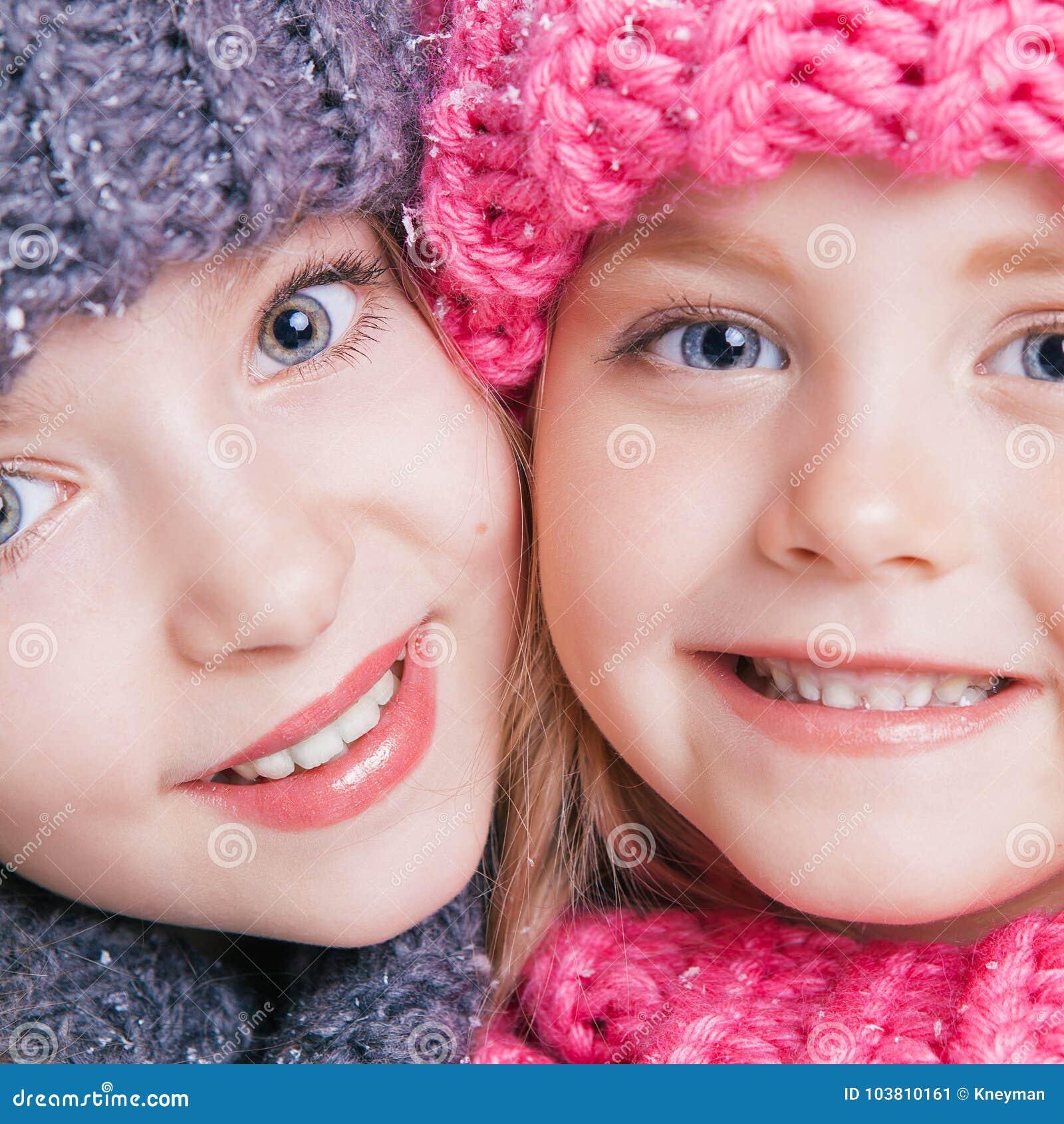 Close-upportret van twee leuke kleine zusters in de winterkleren Roze en grijze hoeden en sjaals Familie