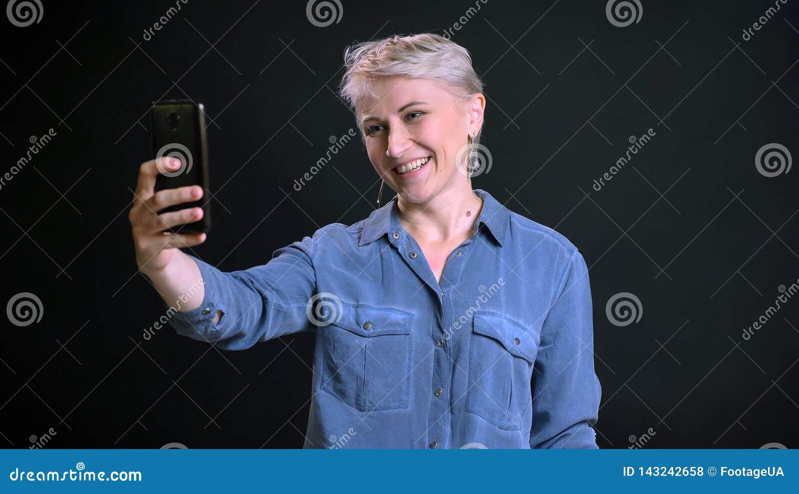 Close-upportret van volwassen vrolijk Kaukasisch wijfje met kort selfies op de telefoon maken en blondehaar die binnen glimlachen