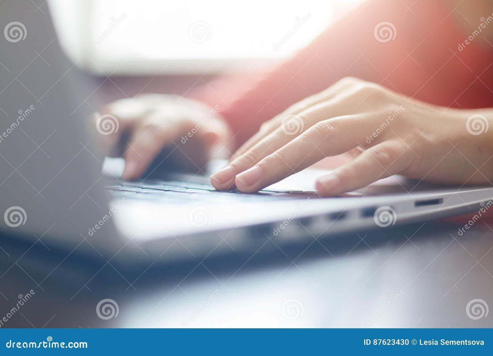 Close-upportret van vrouwen` s handen die op laptop zitting bij de lijst typen Het vrouwelijke onderneemster werken online via la