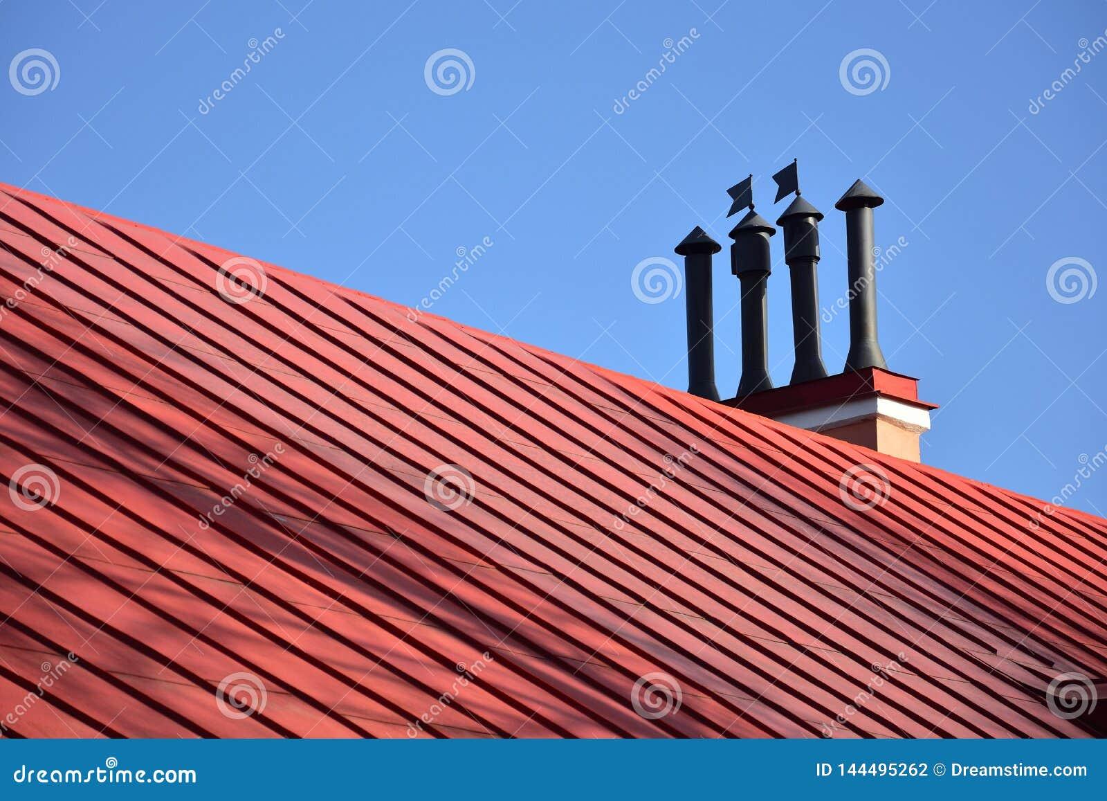 Close-upschoorstenen op het rode dak en de hemel