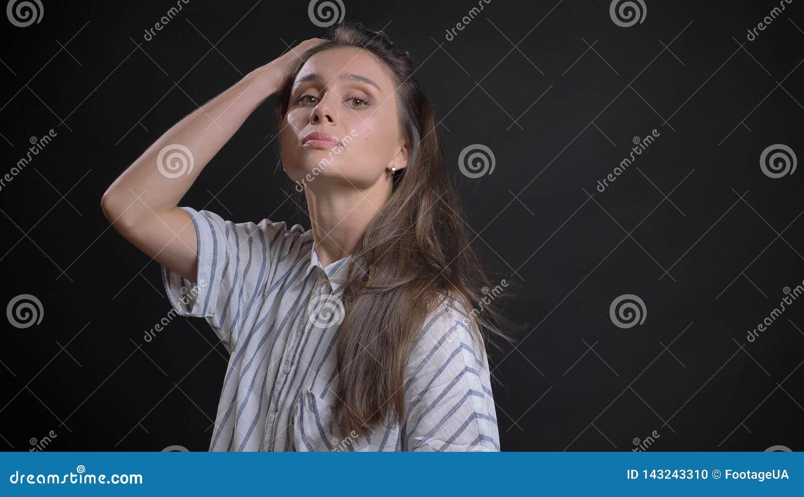 Close-upspruit van jong aantrekkelijk Kaukasisch vrouwelijk mannequin het werpen haar en het stellen voor de camera met