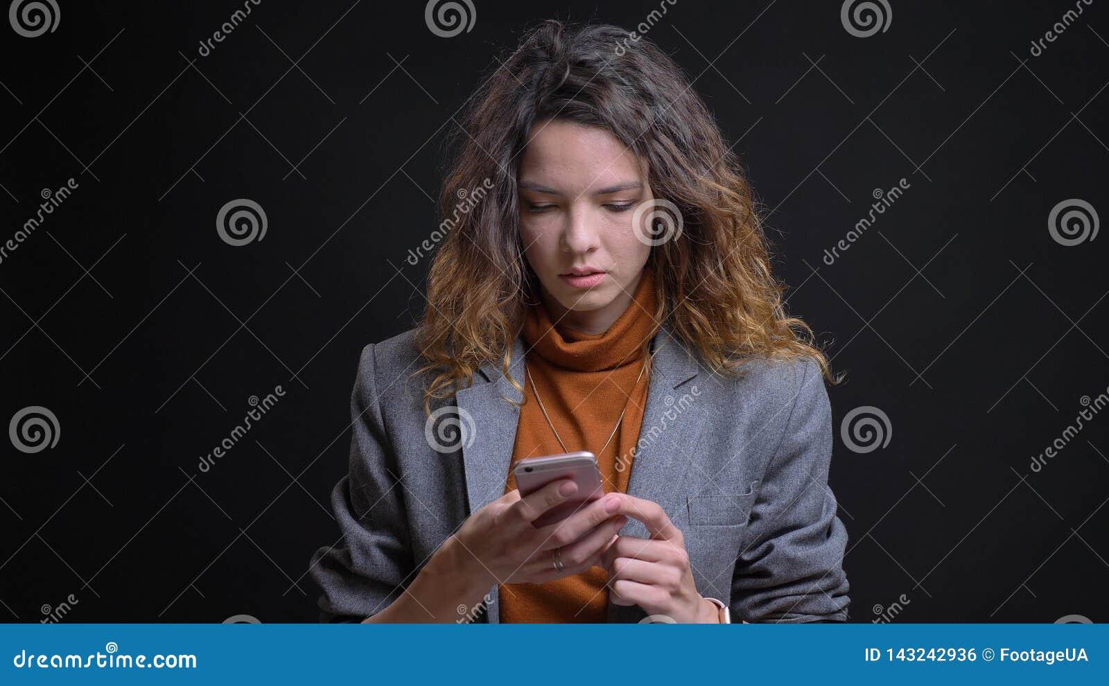 Close-upspruit van jong aantrekkelijk Kaukasisch wijfje die de telefoon voor de camera met geïsoleerde achtergrond met behulp van