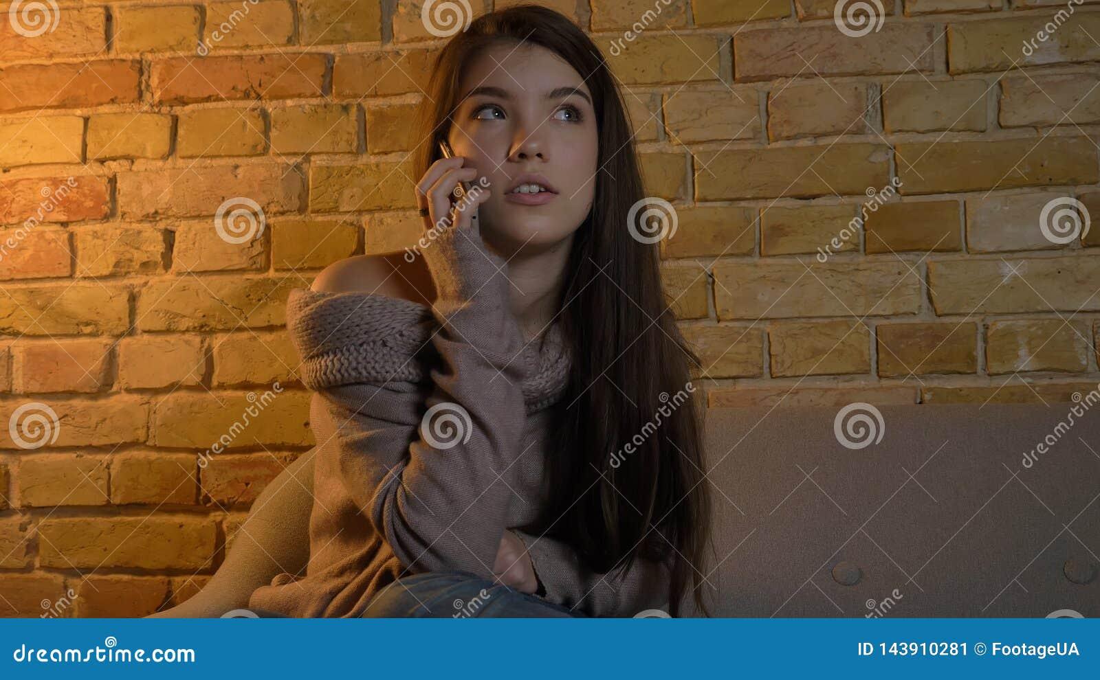Close-upspruit van jong vrij Kaukasisch wijfje die een toevallig gesprek op de telefoon hebben terwijl het rusten op de laag in a