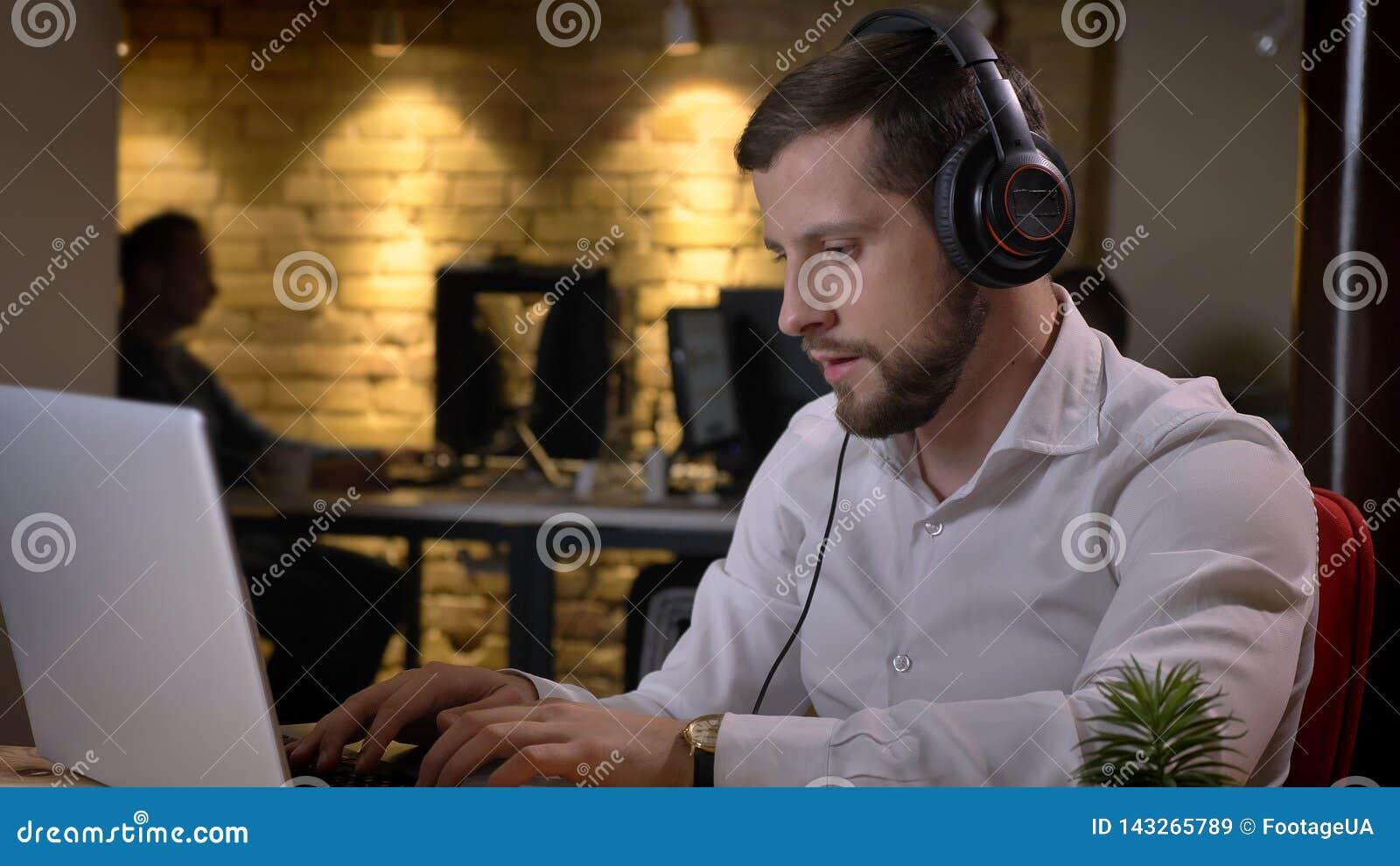 Close-upspruit van volwassen Kaukasische zakenman die in hoofdtelefoons aan muziek luisteren terwijl het typen op laptop binnen i