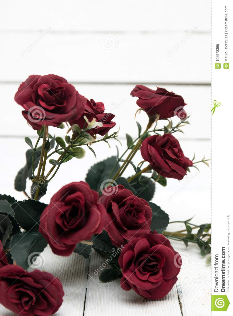 Fake bouquet of red roses isolated on a white background stock close view of fake bouquet of red roses isolated on a white wooden background izmirmasajfo
