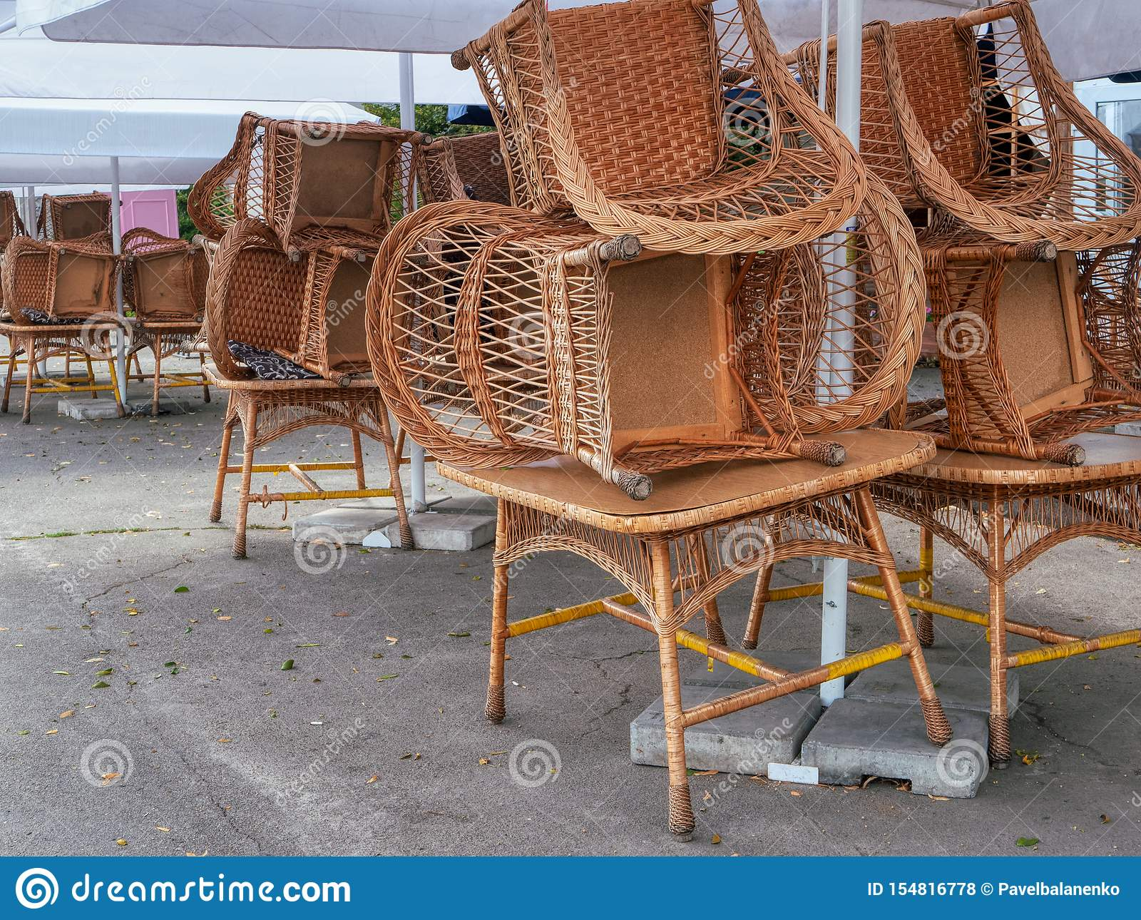 Closed cafe restaurant with rattan whicker chairs, cane-chairs stacked upon tables outdoor