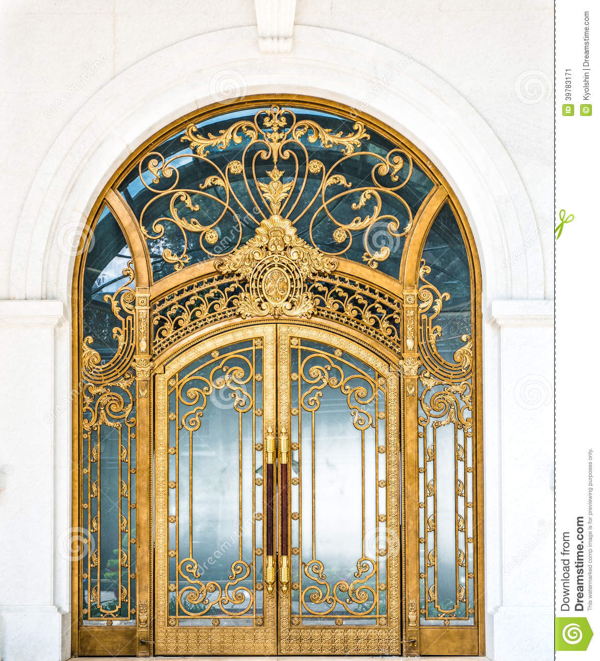 Beautiful arched doorway. Door made of wood, gold and glass reflecting ...