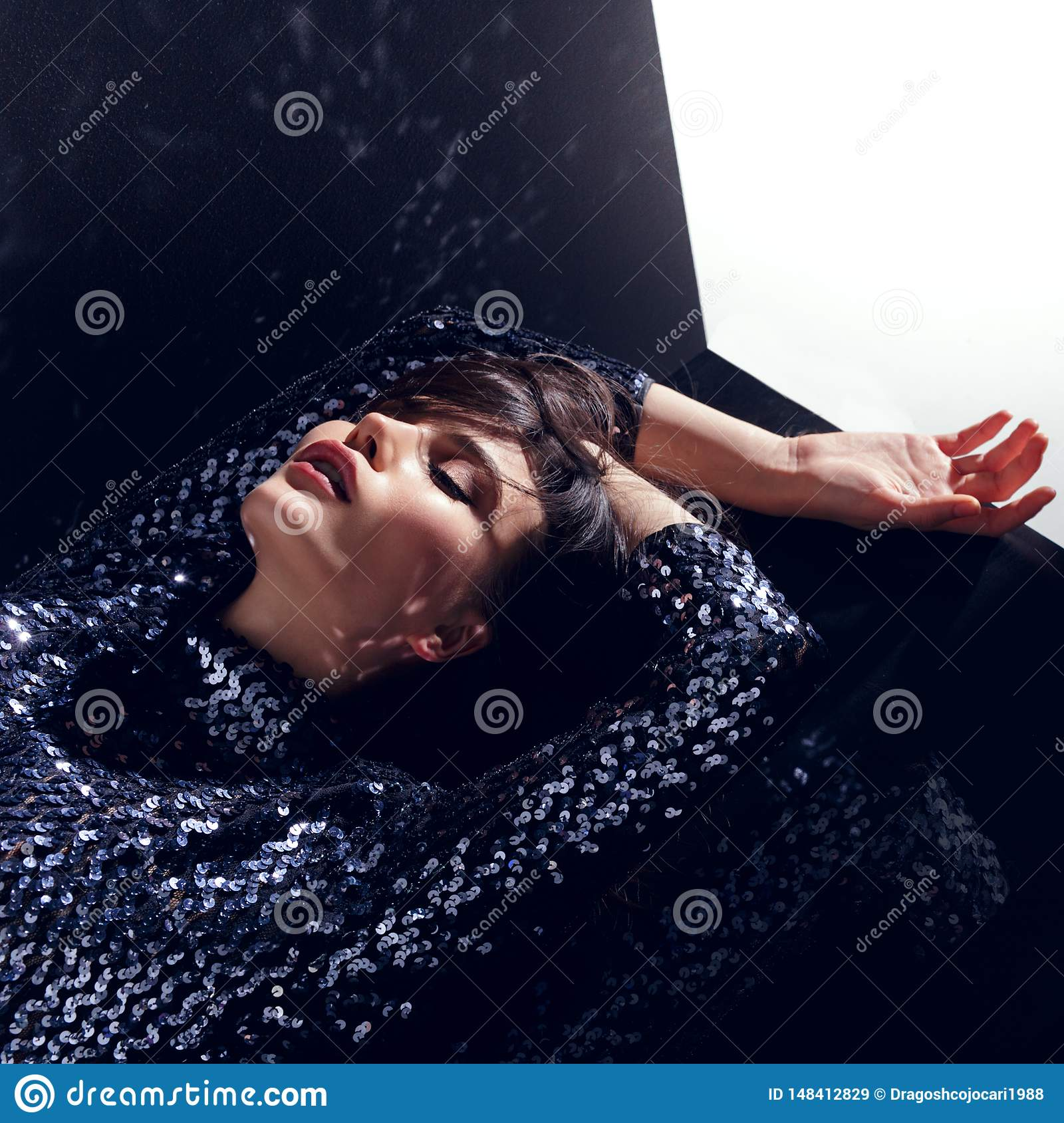 Fashion concept, gorgeous model, with closed eyes in a sequins dress posing in studio, isolated on a black background.