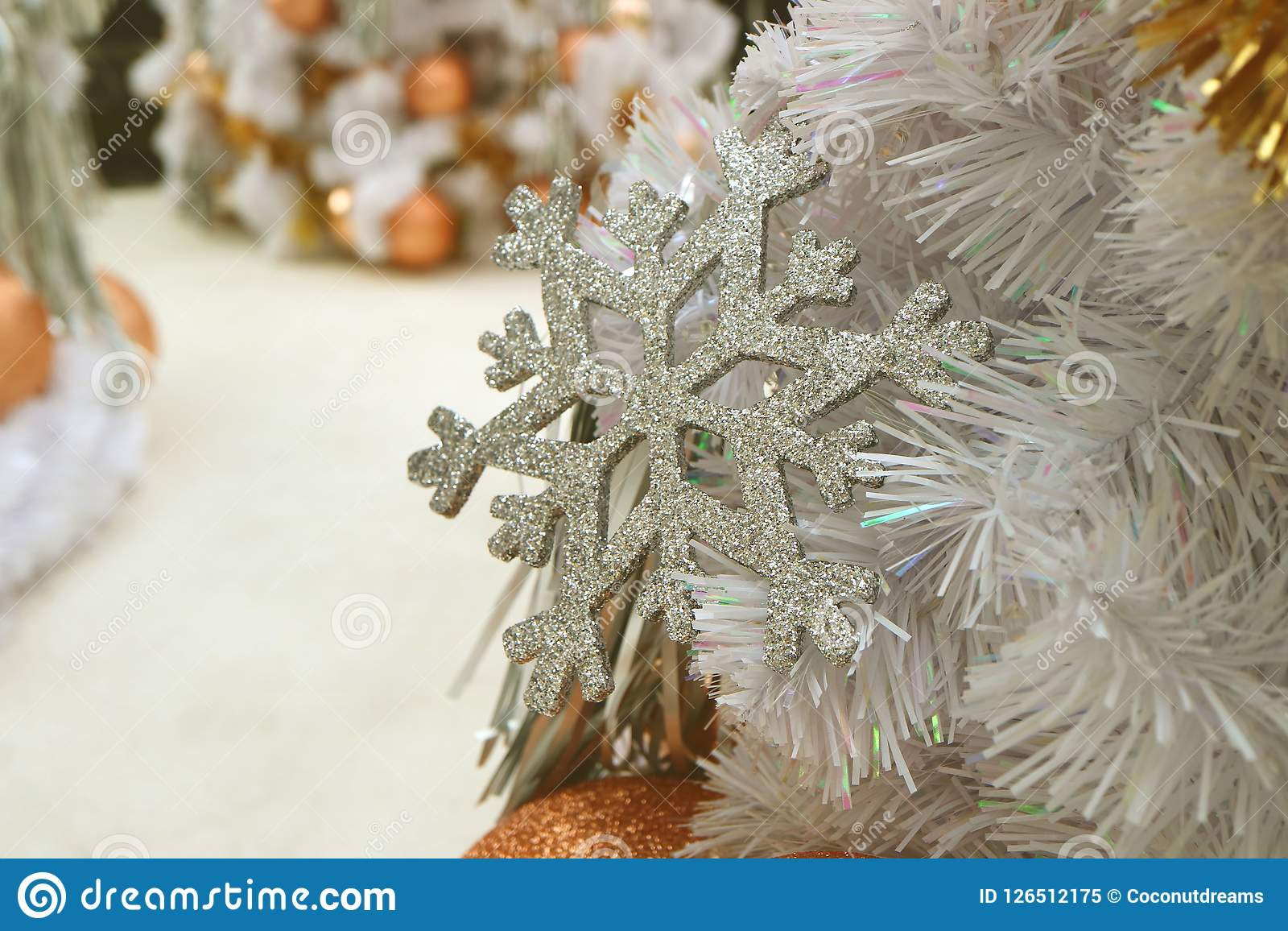 Closed up silver glitter snowflake ornament on white Christmas tree. Selective focus and blurred background Royalty Free Stock Photo