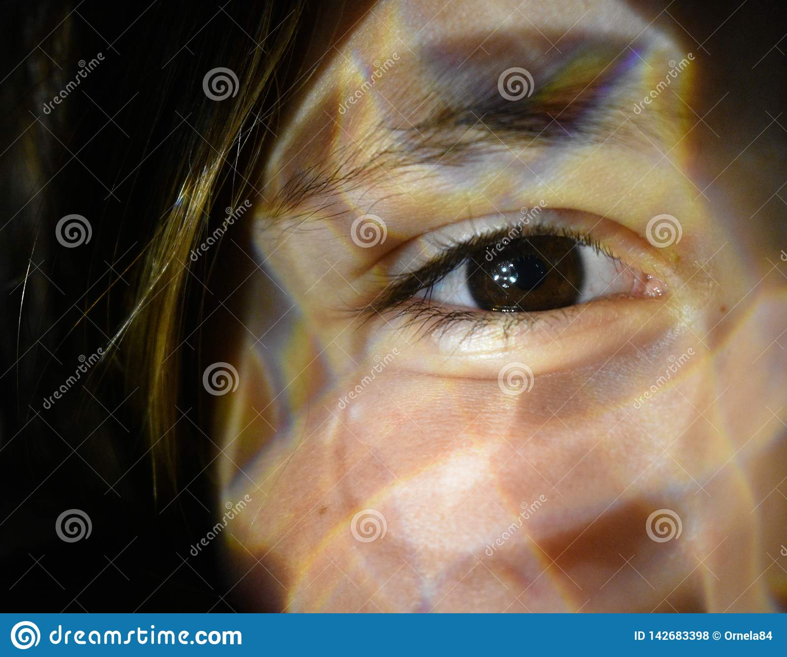 Closed up of a woman eye with light effect on her face