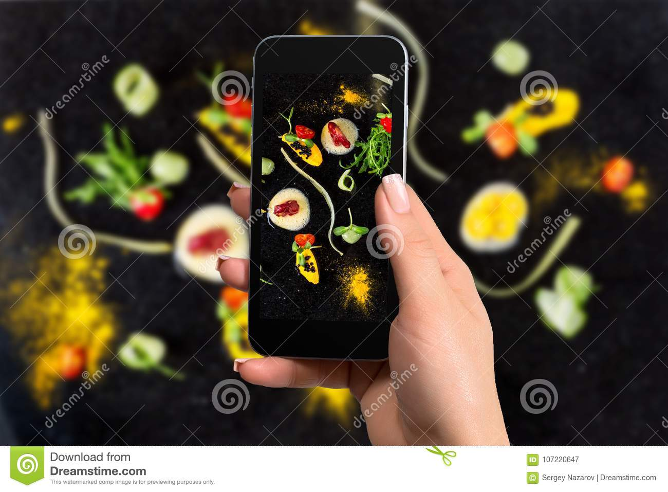 Closely image of female hands holding mobile phone with photo camera mode on the screen abstract gastronomy vanguard
