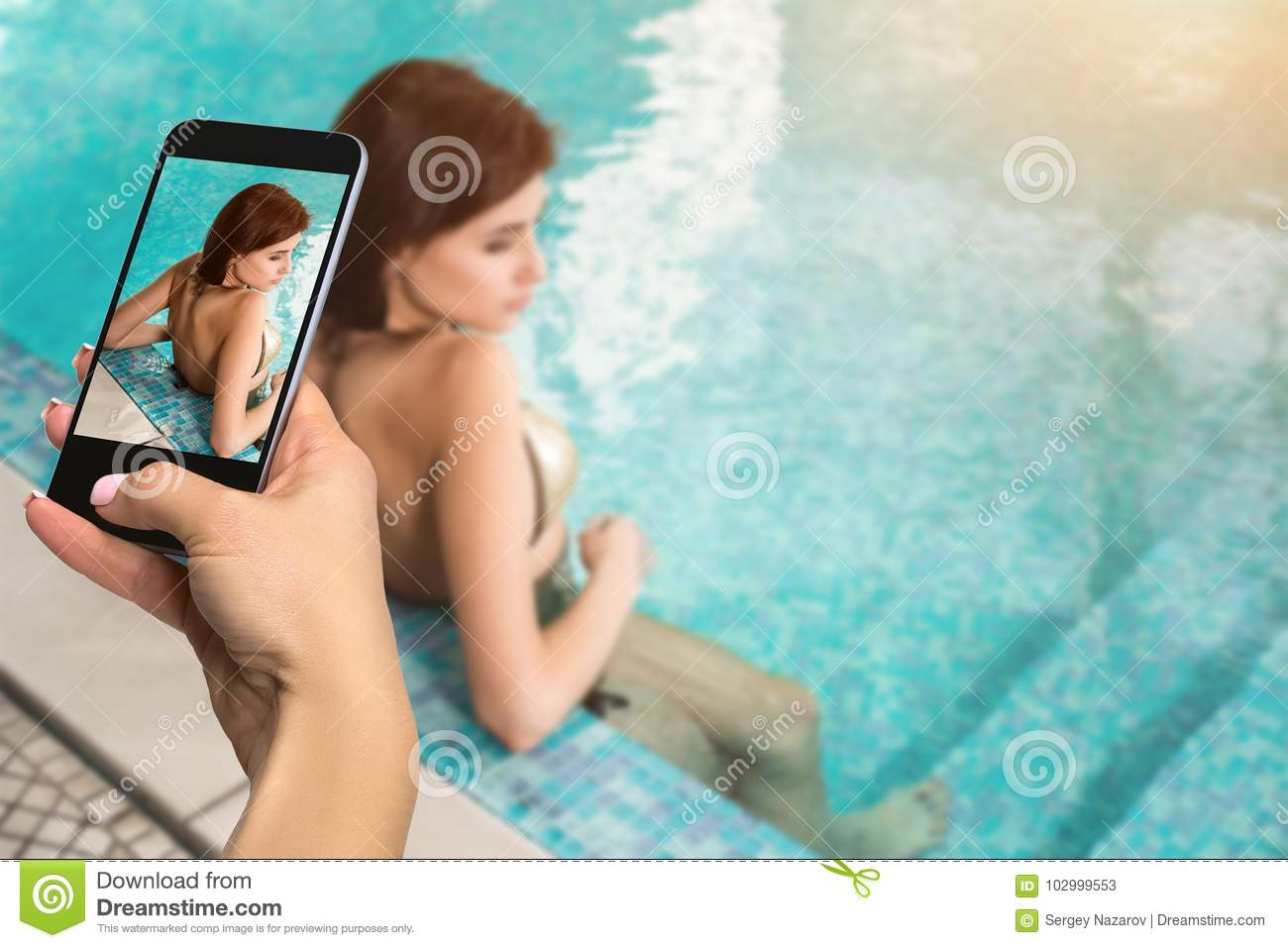 Closely image of female hands holding mobile phone with photo camera mode on the screen. Cropped image of beautiful long