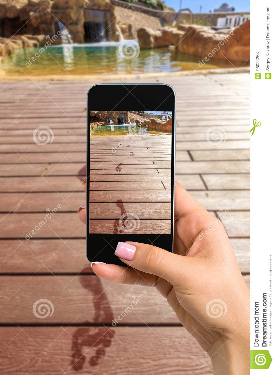 Closely image of female hands holding mobile phone with photo camera mode on the screen. Cropped image of footprints on