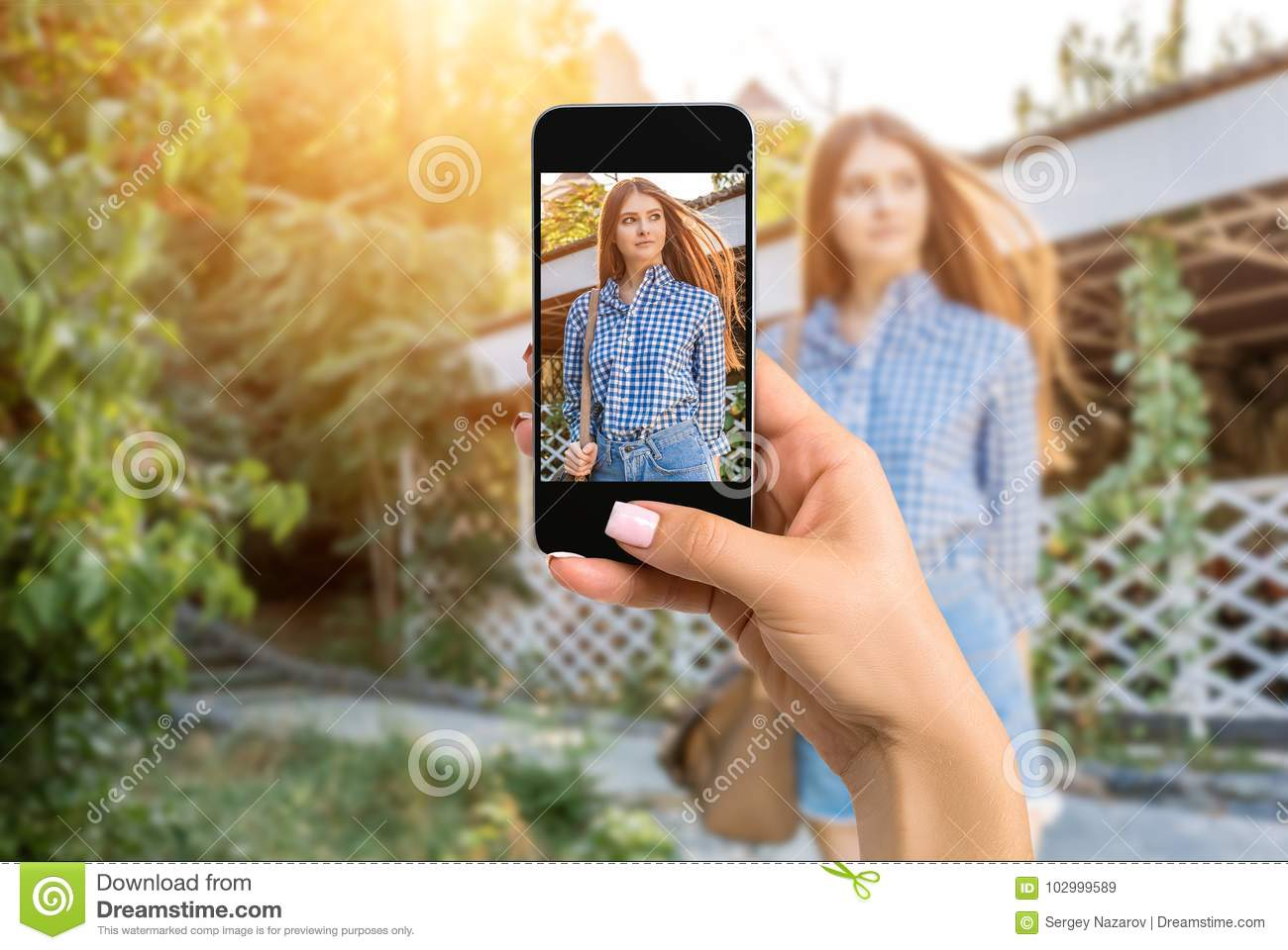 Closely image of female hands holding mobile phone with photo camera mode on the screen. Cropped image of portrait of a