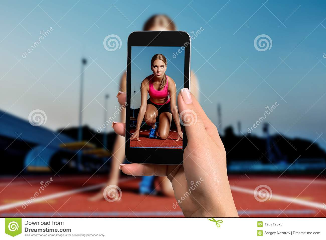 Closely image of female hands holding mobile phone with photo camera mode on the screen. Cropped image of running woman.