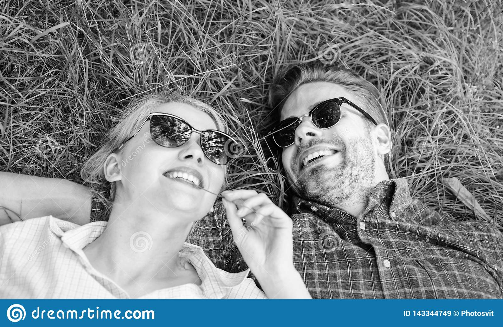 Closer to nature. Nature fills them with freshness and inspiration. Man unshaven and girl lay on grass meadow. Guy and