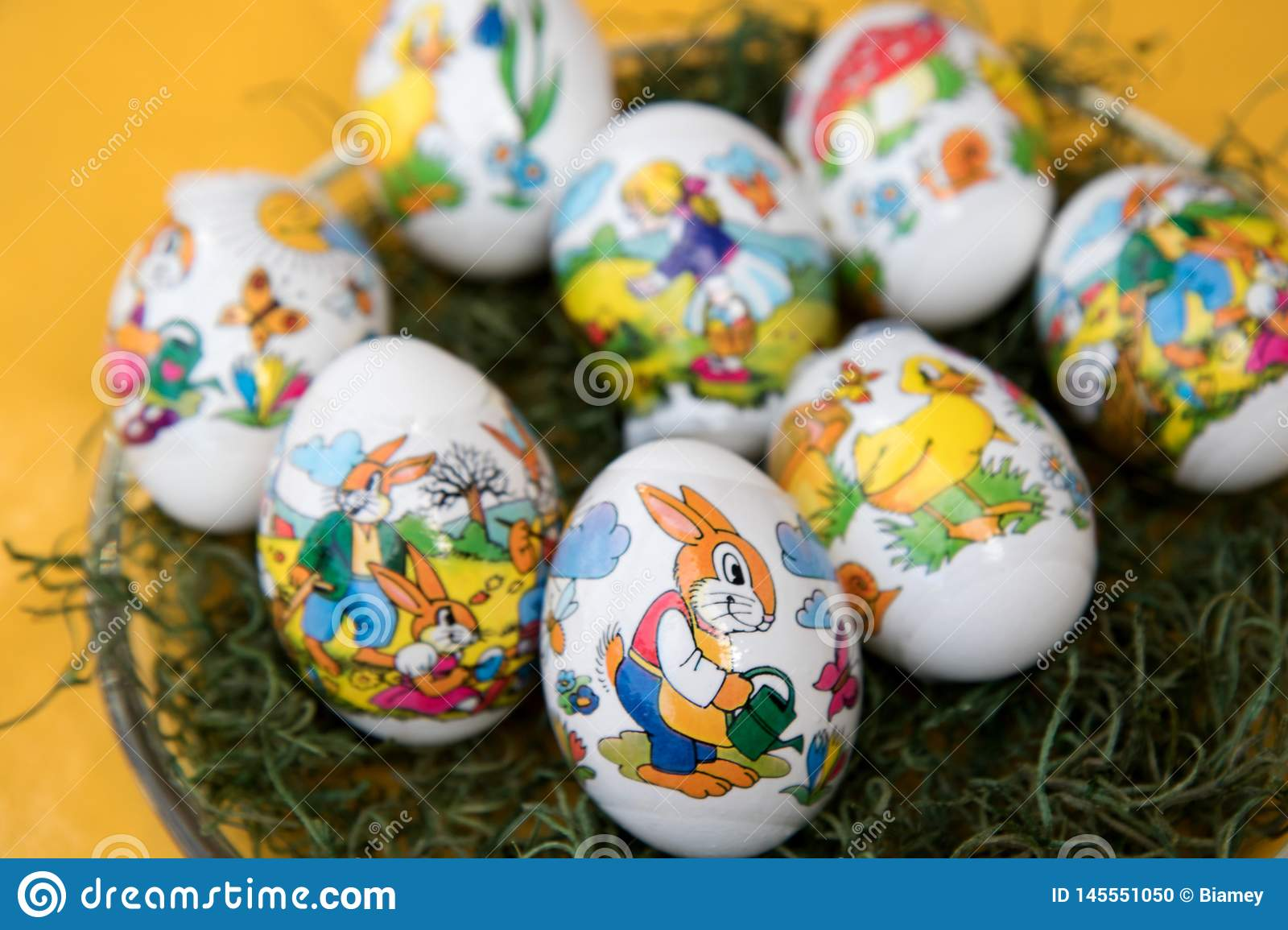 Closer view on an easter egg with an easter bunny on a yellow tablecloth