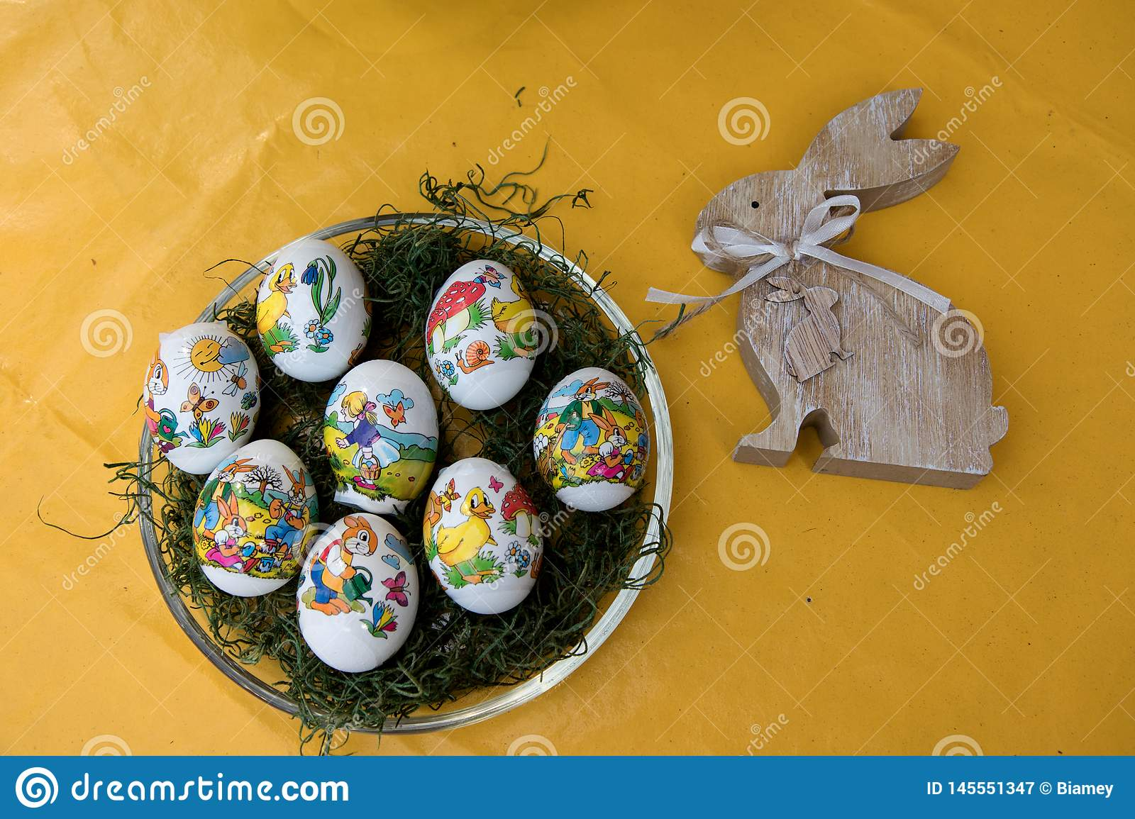 Closer view on easter eggs and a wooden easter bunny on a yellow tablecloth with copy space