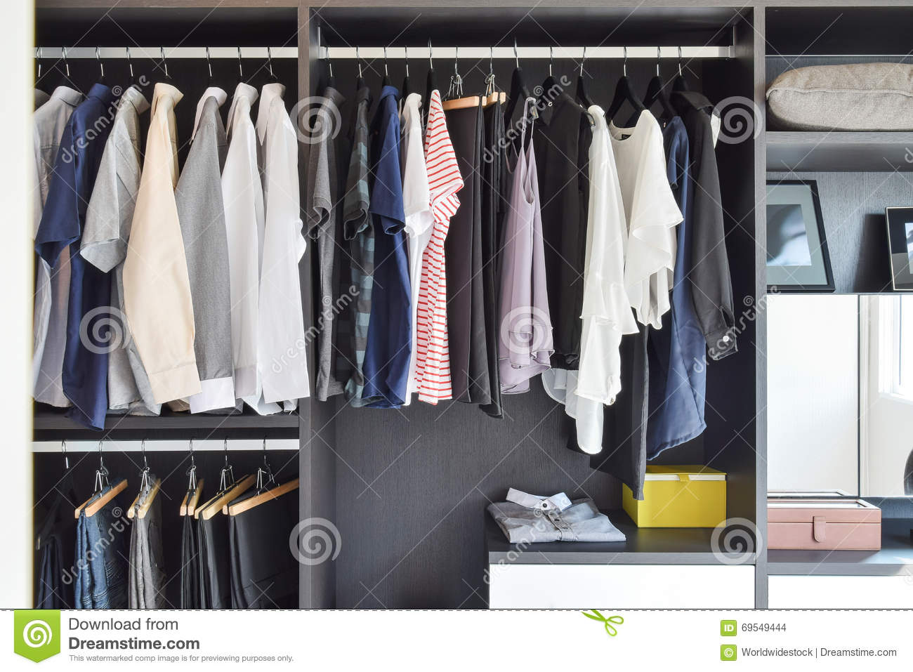Closet with row of cloths hanging in black wardrobe