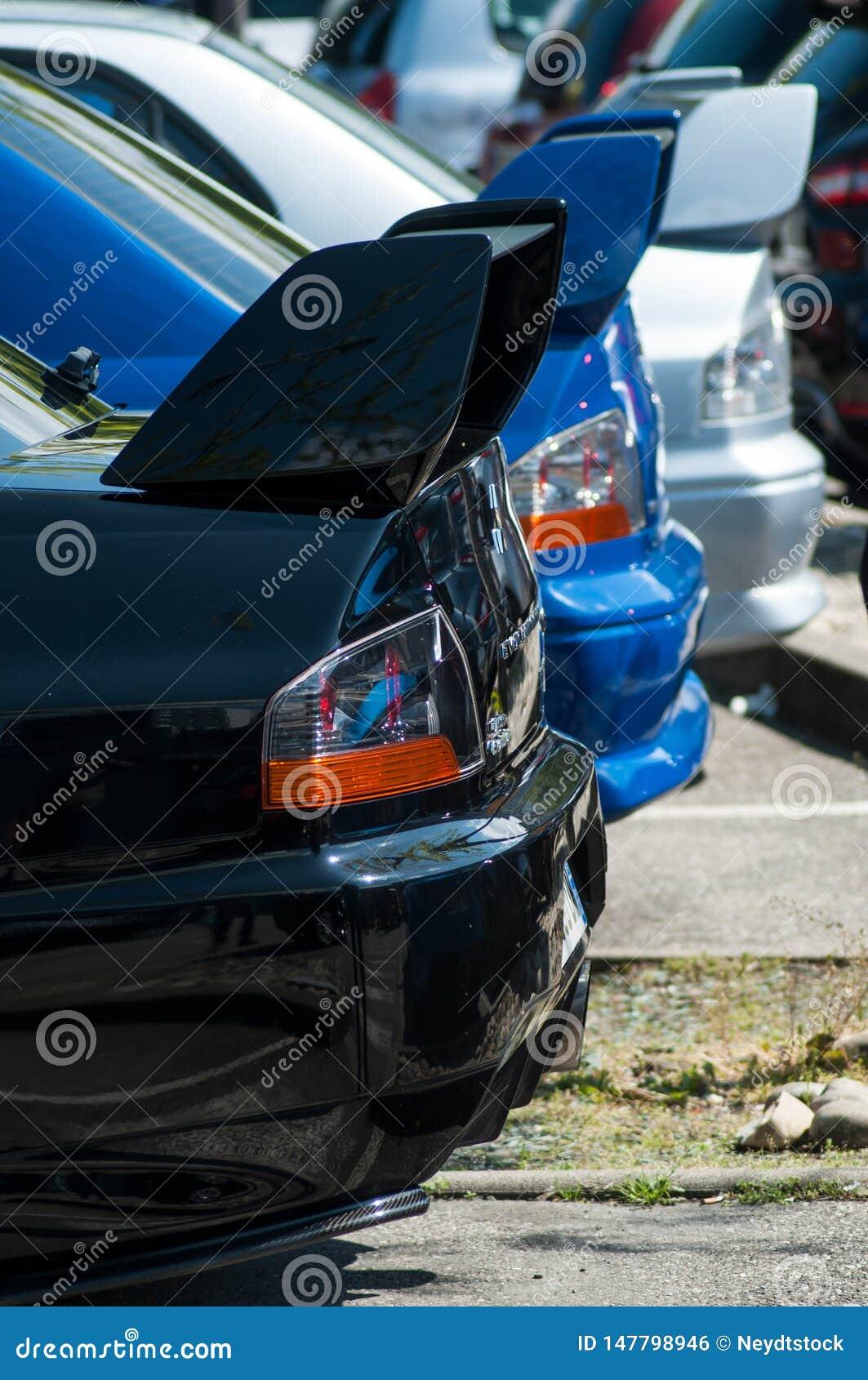Closeup av baksidan av svarta, blåa och gråa Subaru Impreza som parkeras i gatan