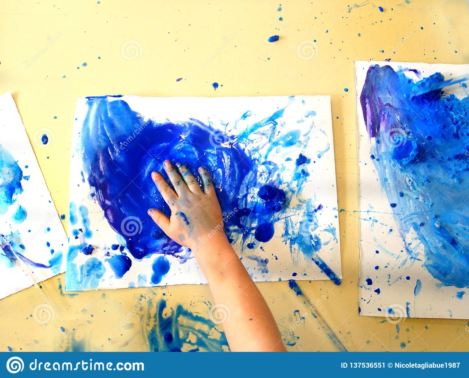 Closeup av barnhänder som målar under en skolaaktivitet - ismålning - som lär vid att göra, utbildning och konst, konstterapi