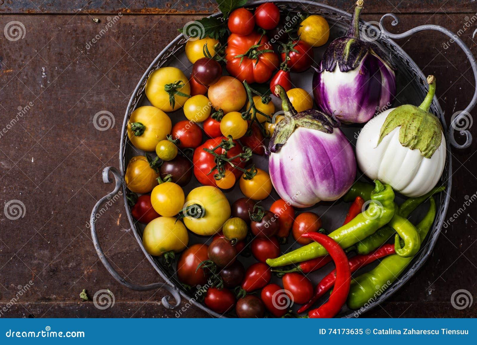 Closeup av den metalliska korgen med nya grönsaker