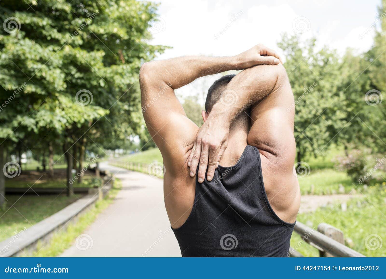 Closeup av den tillbaka idrotts- mannen som gör elasticiteter, innan att öva,