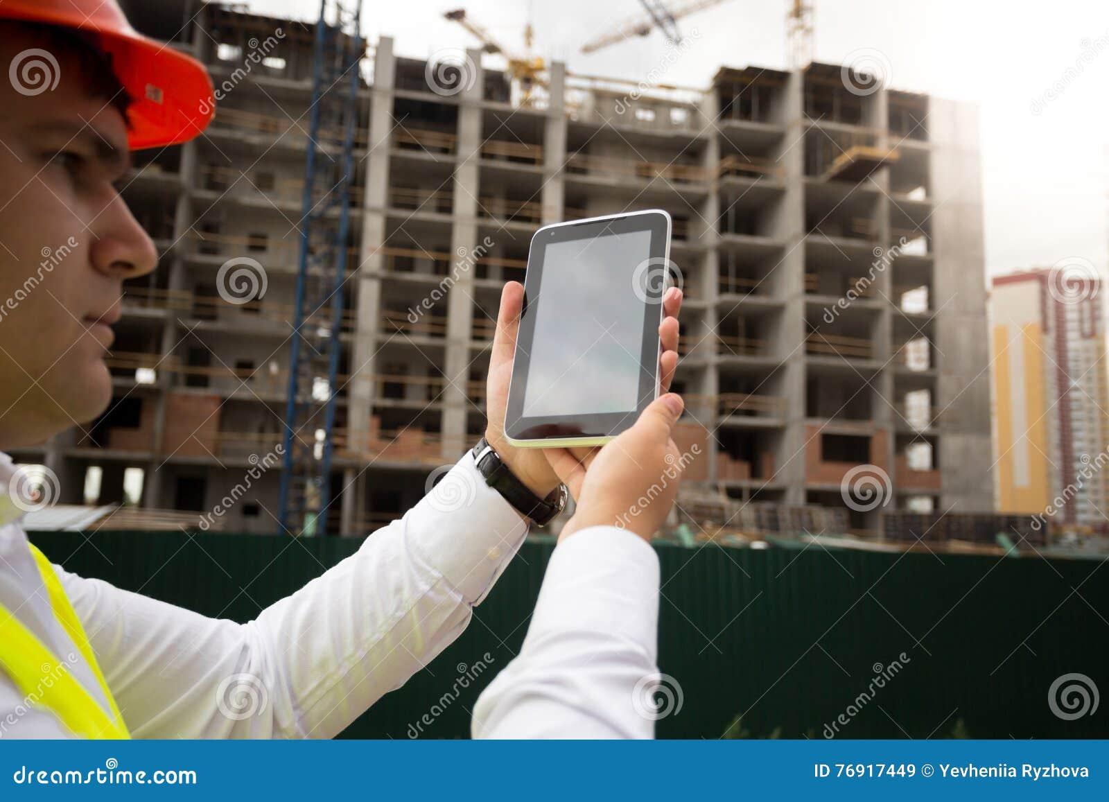Closeup av den unga konstruktionsteknikern på byggnadsplats genom att använda di