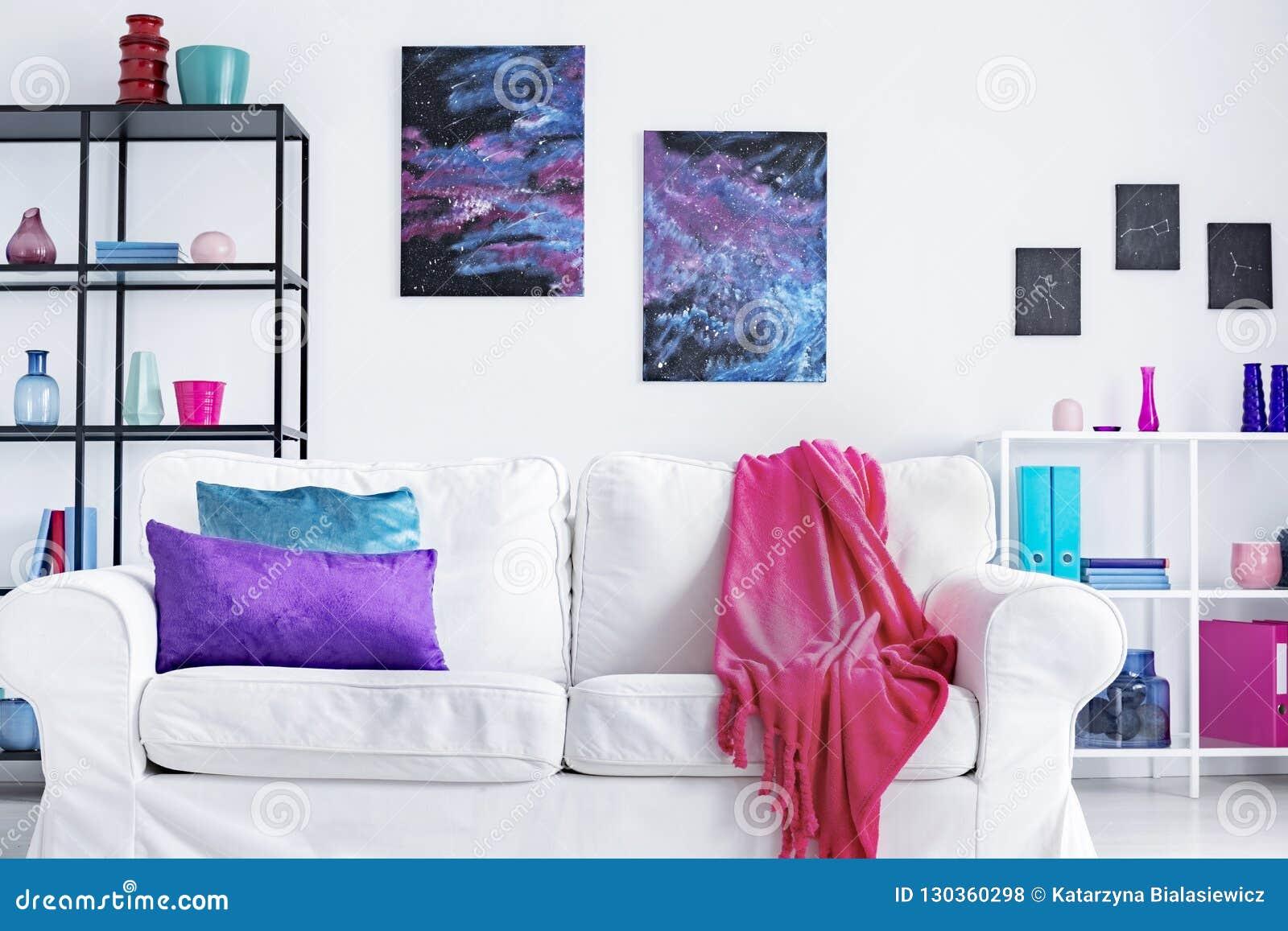 Closeup av den vita bekväma soffan med rosa färgfilten och purpurfärgade och blåa kuddar i den moderna vardagsruminre, verkligt f