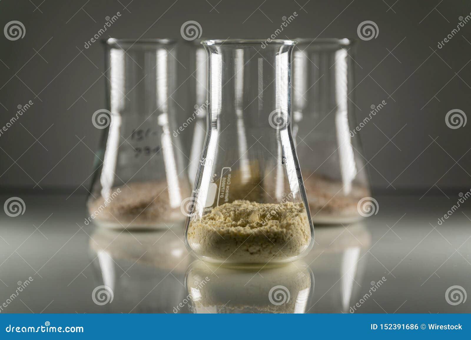 Closeup av exponeringsglaskemiflaskor med brunt kemiskt pulver i dem