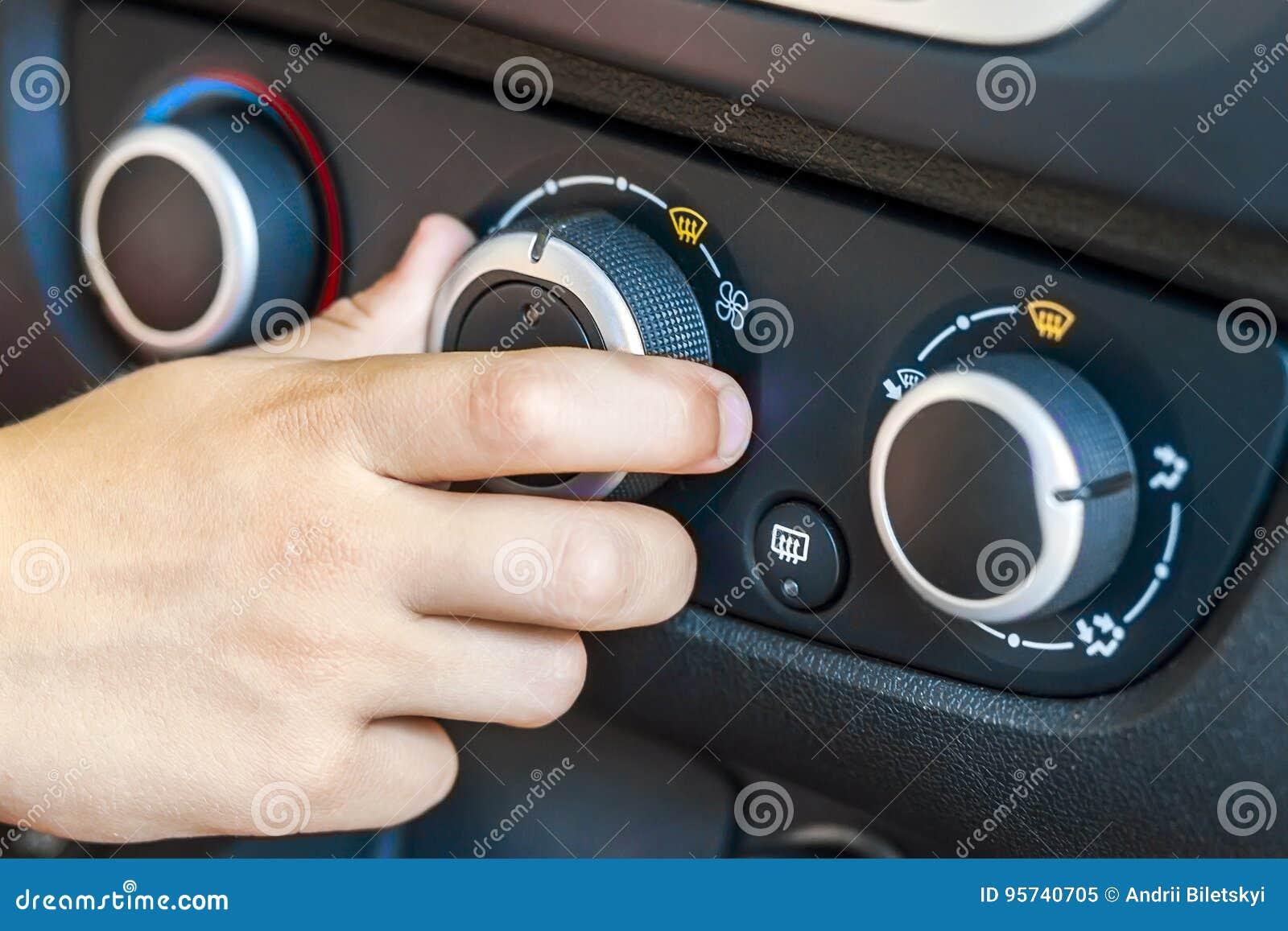 Closeup av för biltemperatur för mänsklig hand en roterande kontroll, shallo