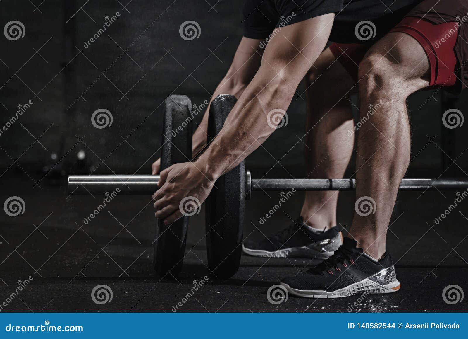 Closeup av idrottsman nen som förbereder sig för lyftande vikt på crossfitidrottshallen Skivstångmagnesiaskydd Övande funktionell