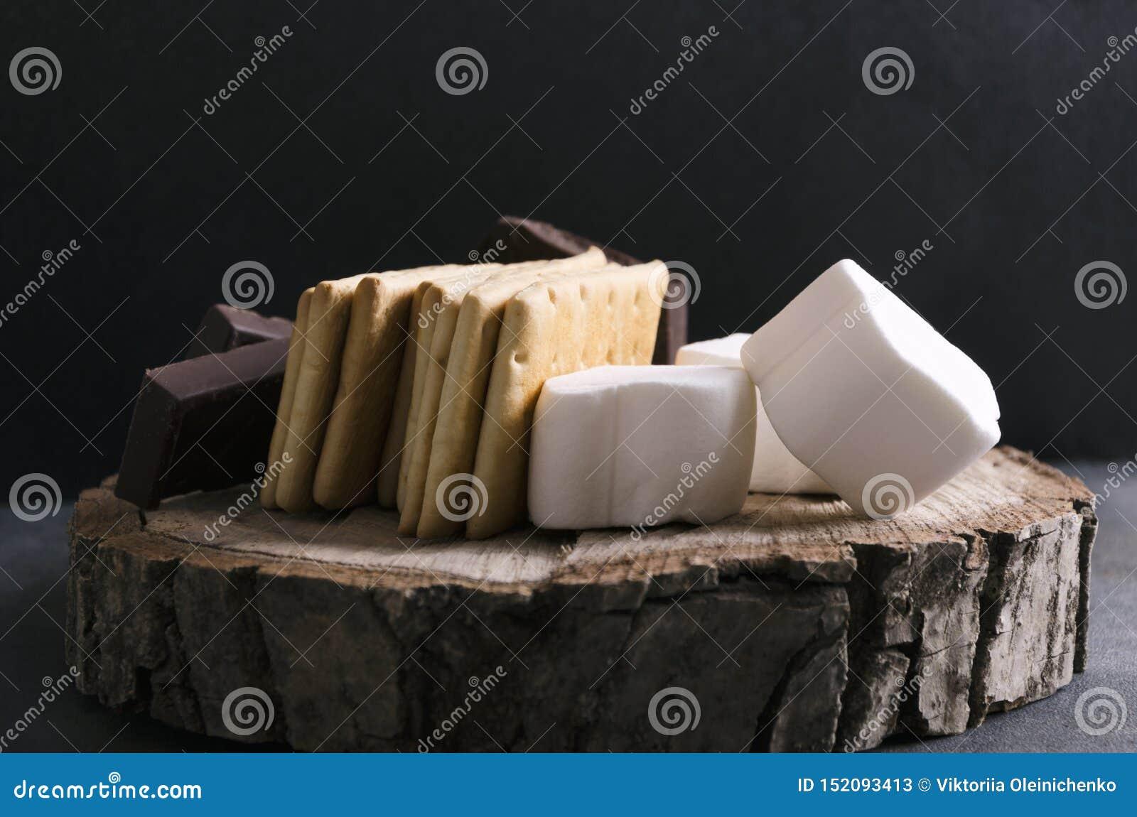 Closeup av ingredienser för smakliga s sedvänjor med chokladnad-marshmallower på trämagasinet, lantligt lynne