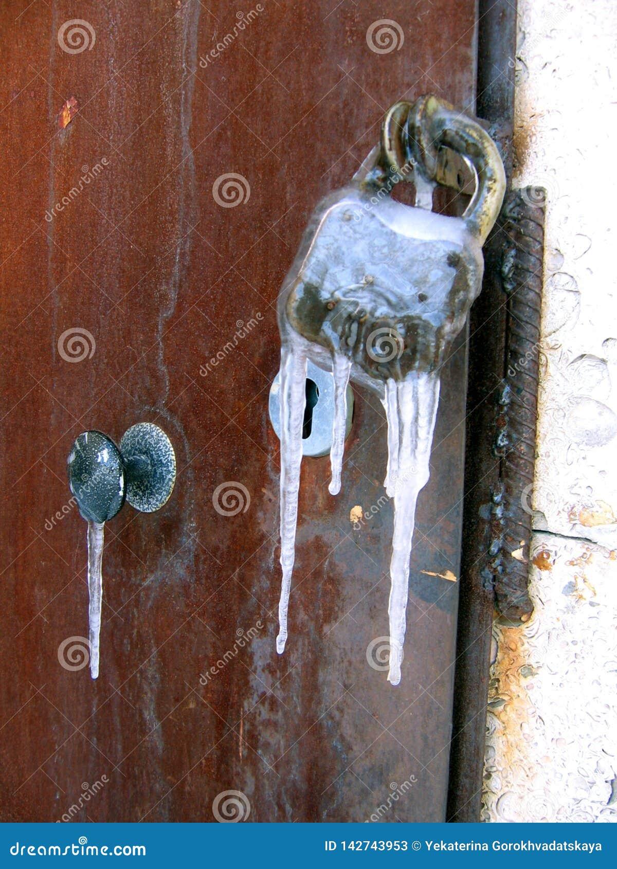 Closeup av järndörren med det gamla rostiga låset som frysas med istappar